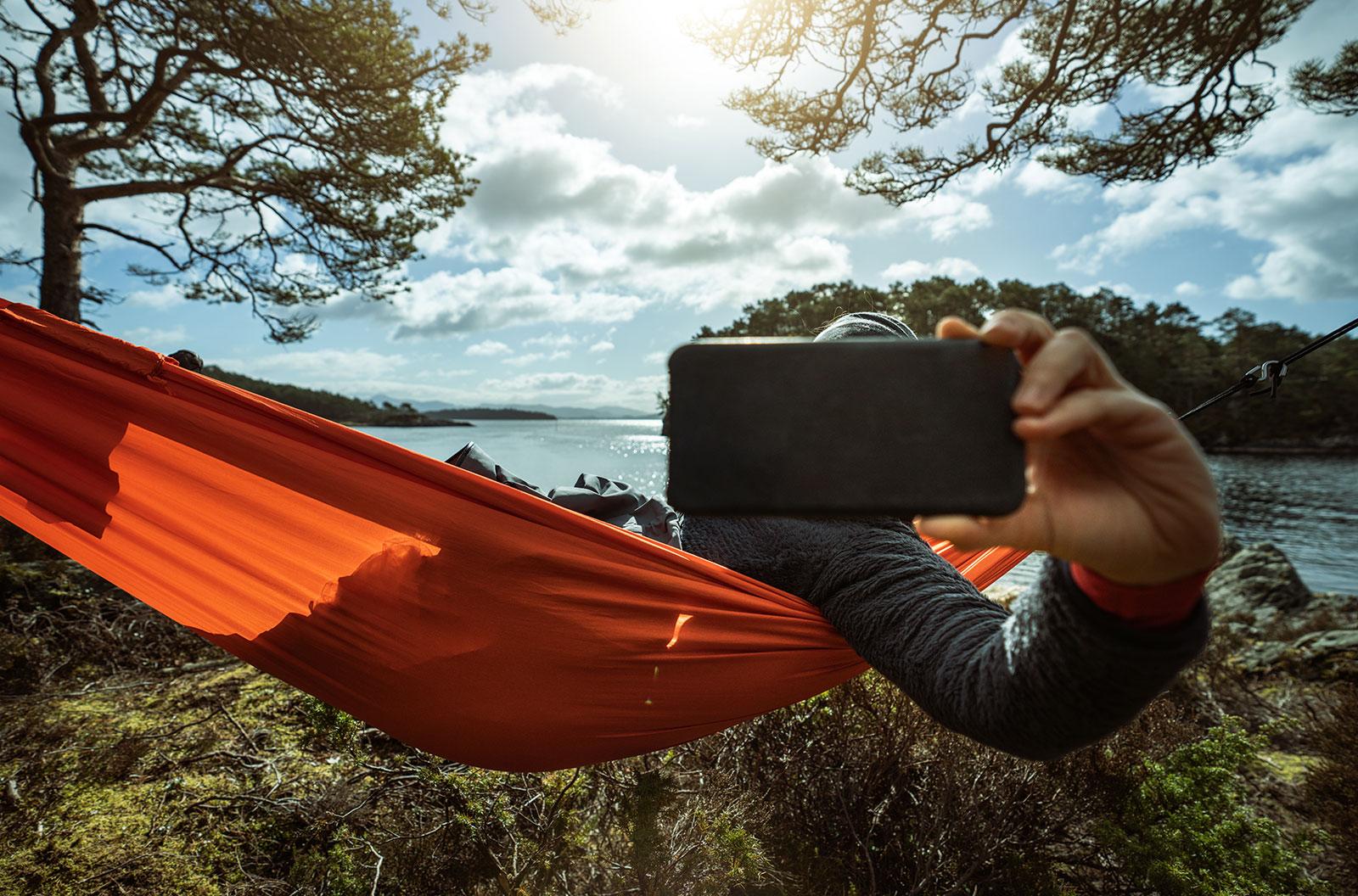 Man on a hammock outdoors taking a selfie