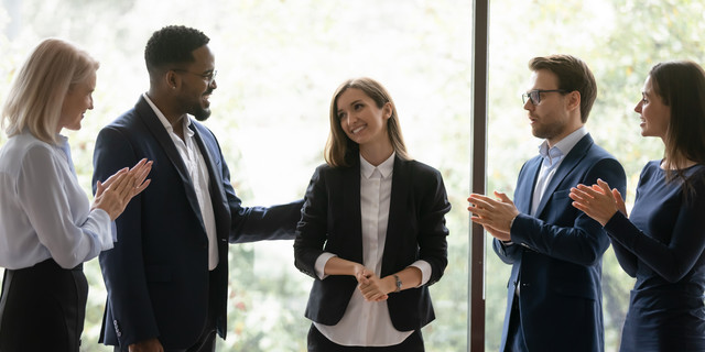 Multiracial colleagues applaud congratulating female leader with success