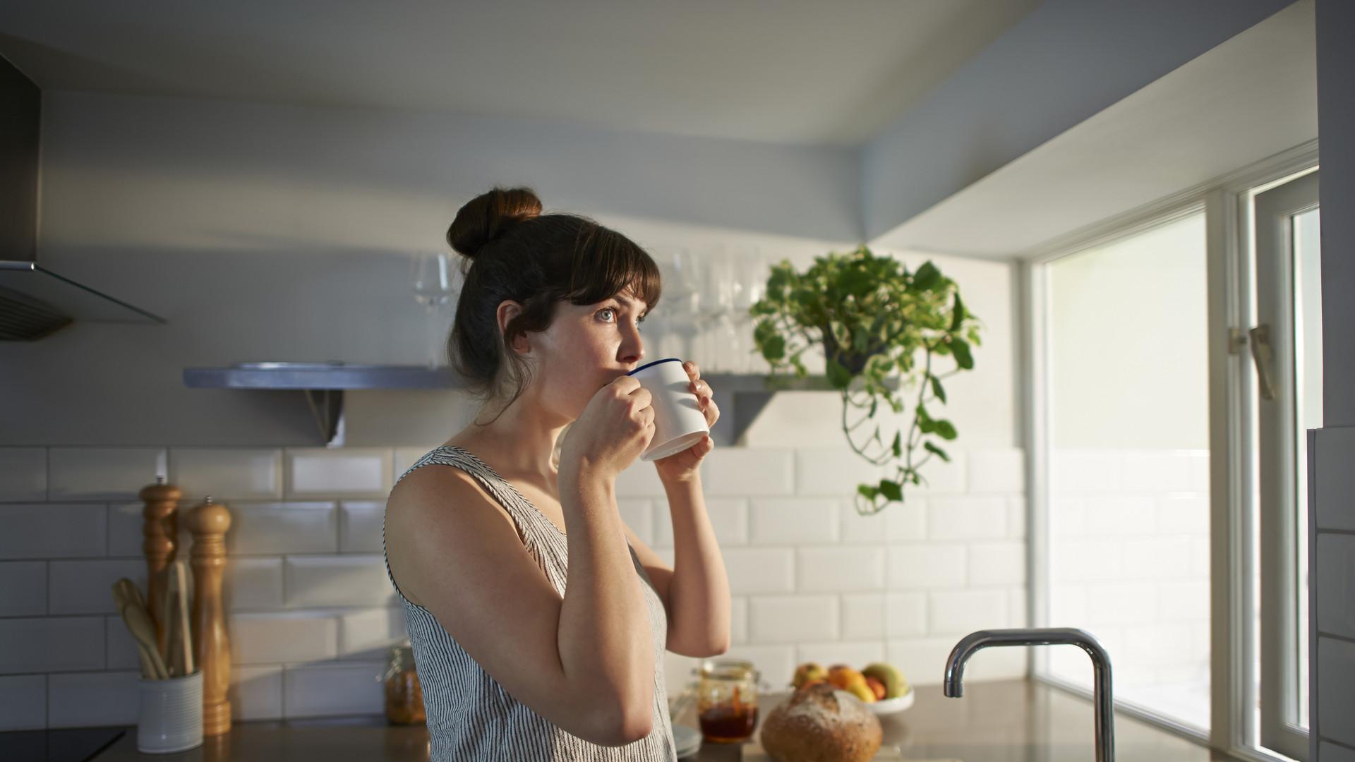 Woman drinking from mug in zero waste kitchen.