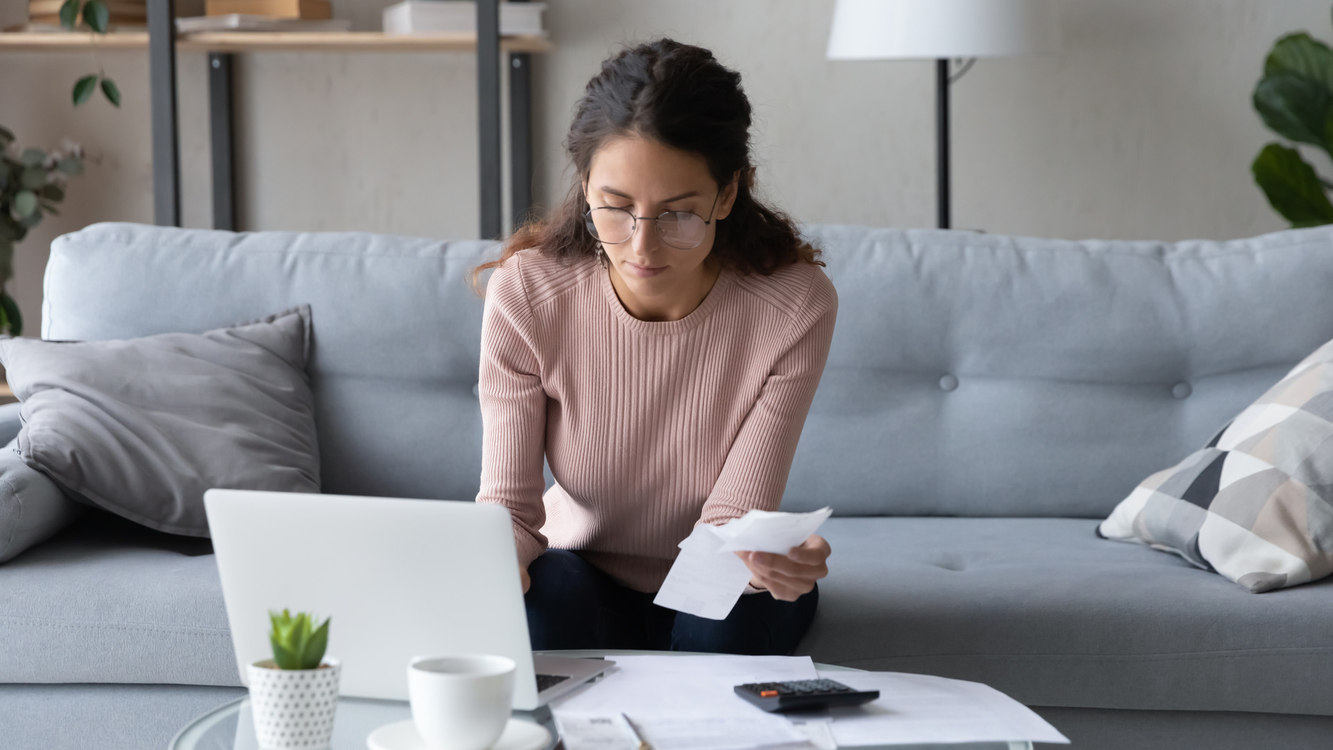Serious female manage family finances using laptop