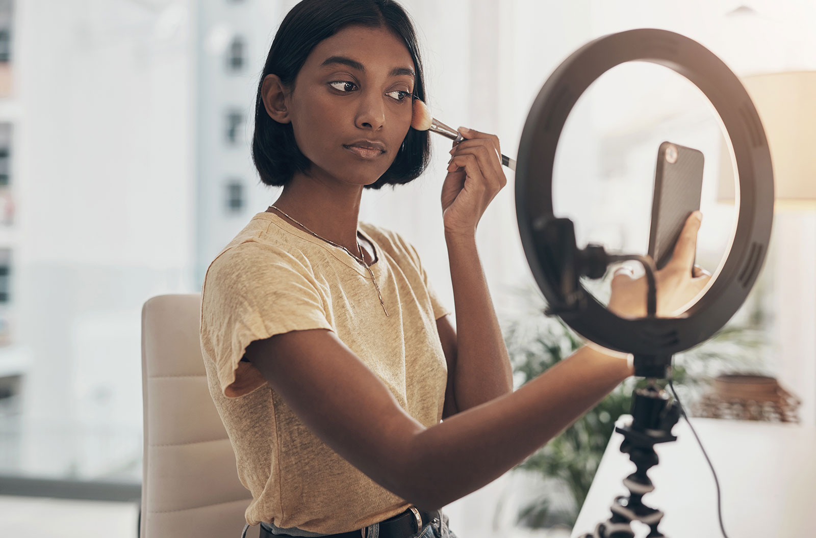 A young woman applying makeup while filming a beauty tutorial with her phone