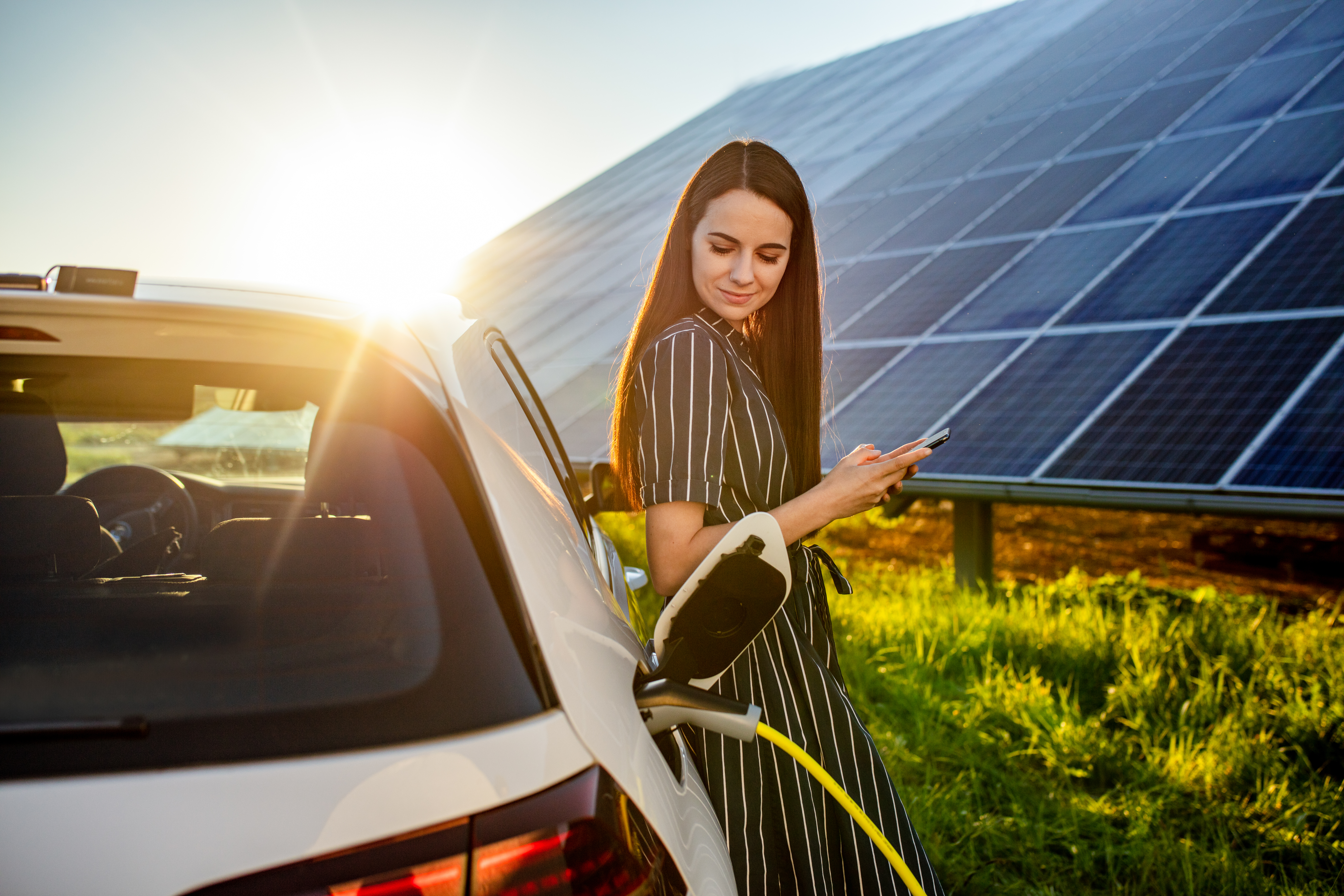 Woman waiting for electric car to charge and solar panels in background