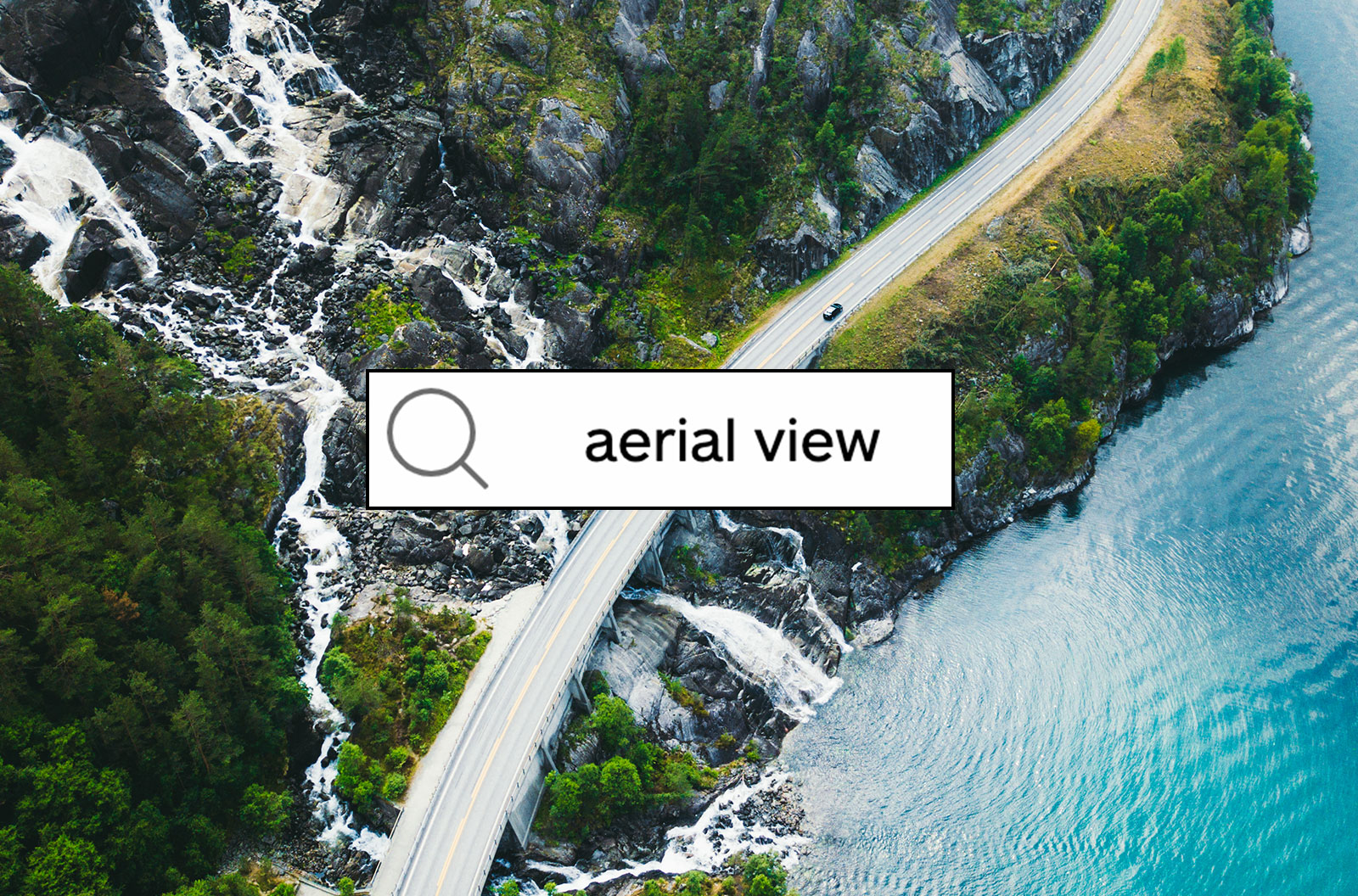 Aerial view of scenic mountain road with car, sea and waterfall in Norway