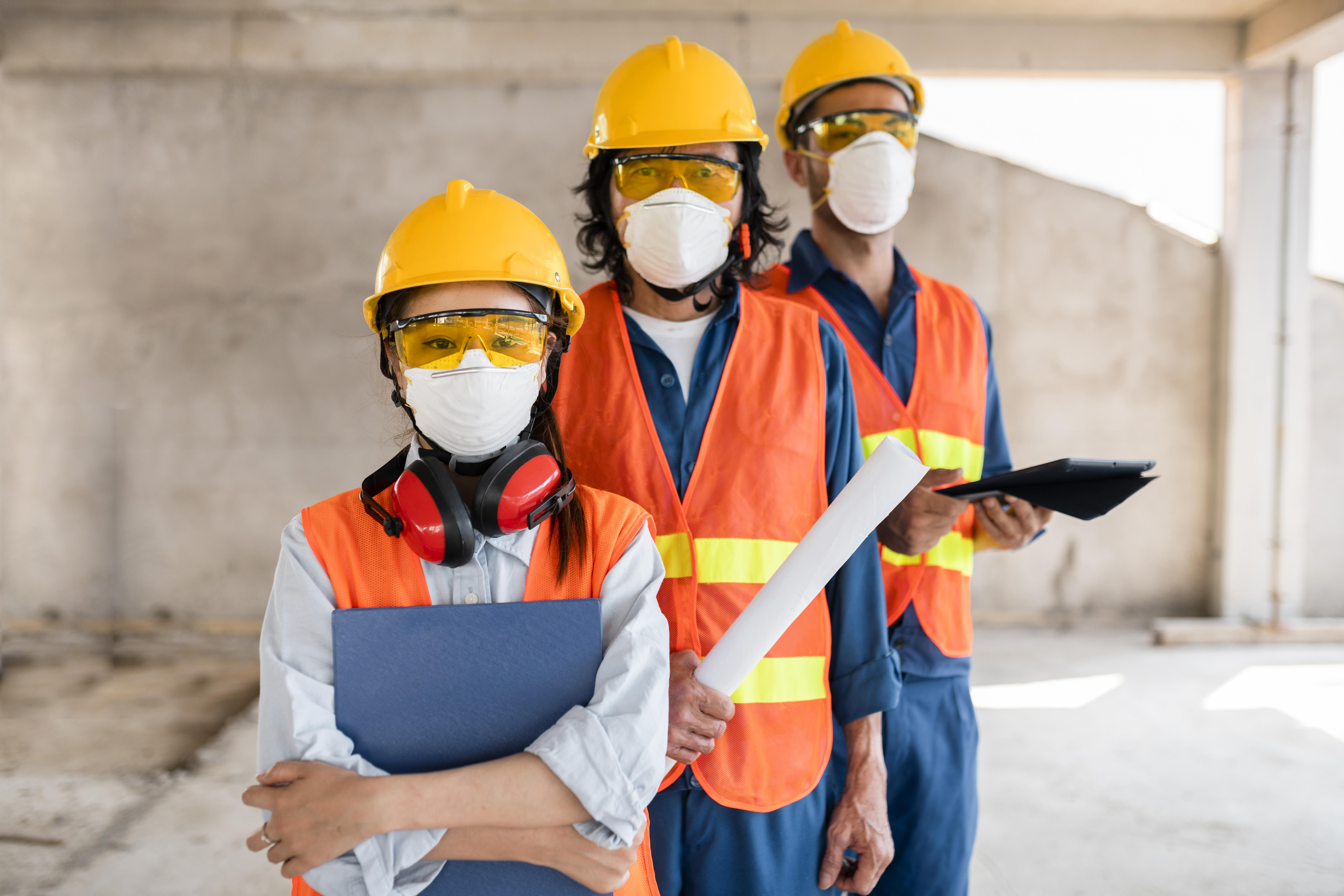 colleagues-with-safety-equipment-working-with-blueprints.jpg