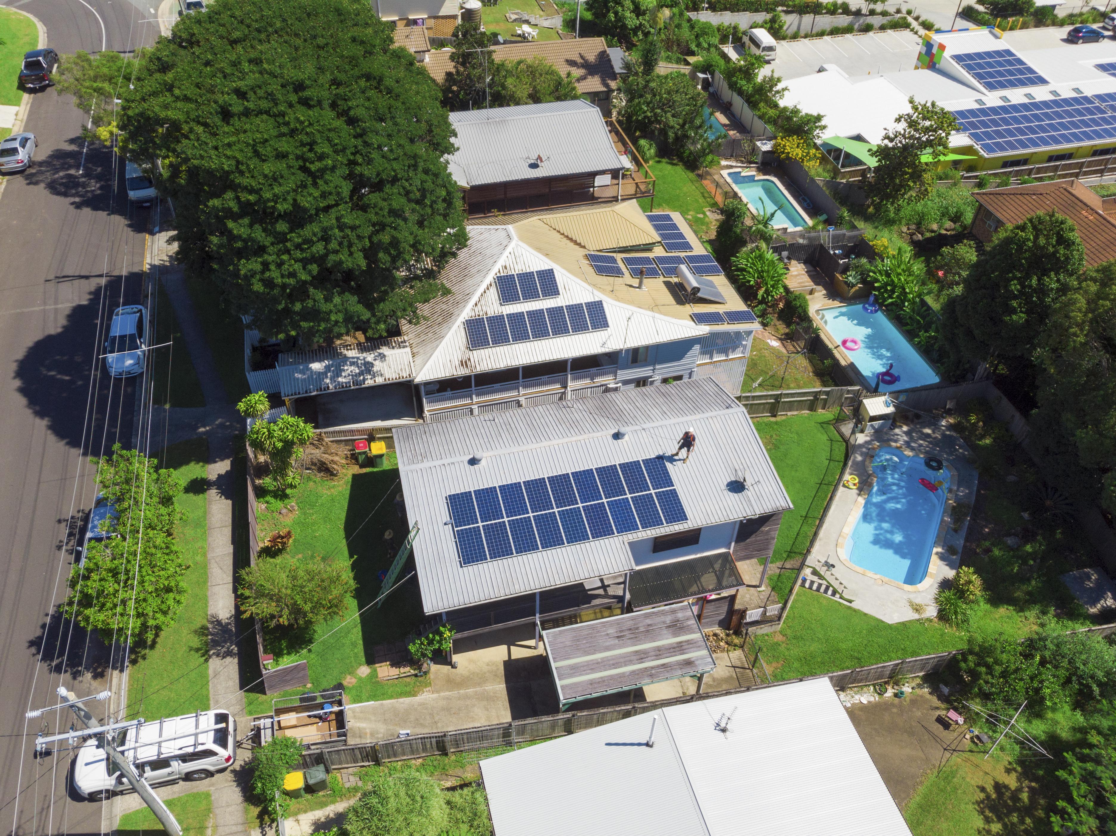 Aerial shot of solar panel technician installing solar panels on roof