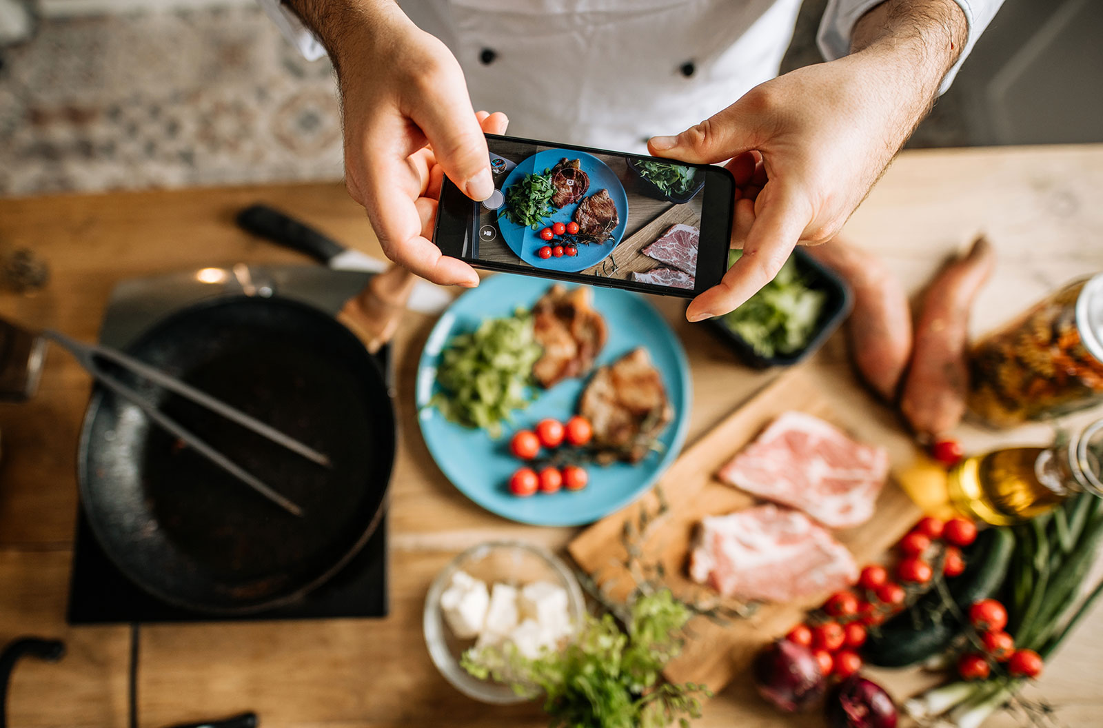 Blogger taking photo of cooked meal on the table with his phone