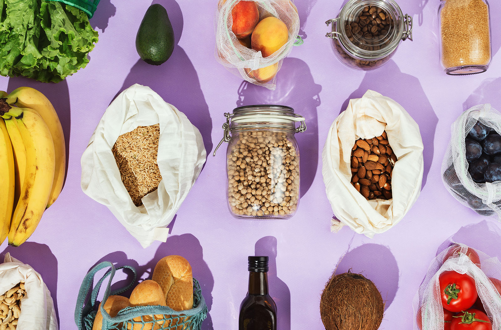 Fruits, greens and vegetables in mesh bags and glass jars on against a purple background
