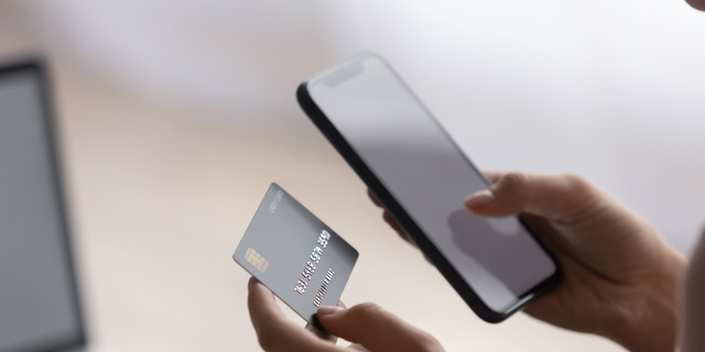 Female hands holding plastic card and cellphone purchasing goods online