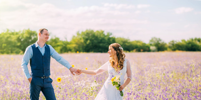 married couple walking in the field of purple flowers, the bride leads the groom behind her, the girl holds the guy by the hand, smiles, smoking hair, a woman in a white wedding dress, blue suit