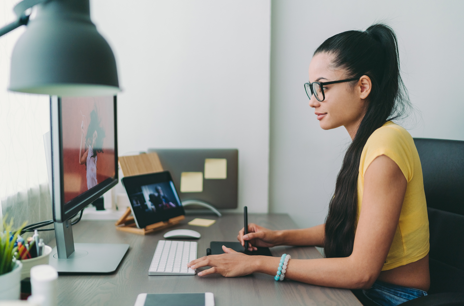 Young woman writing down notes at her home office desk
