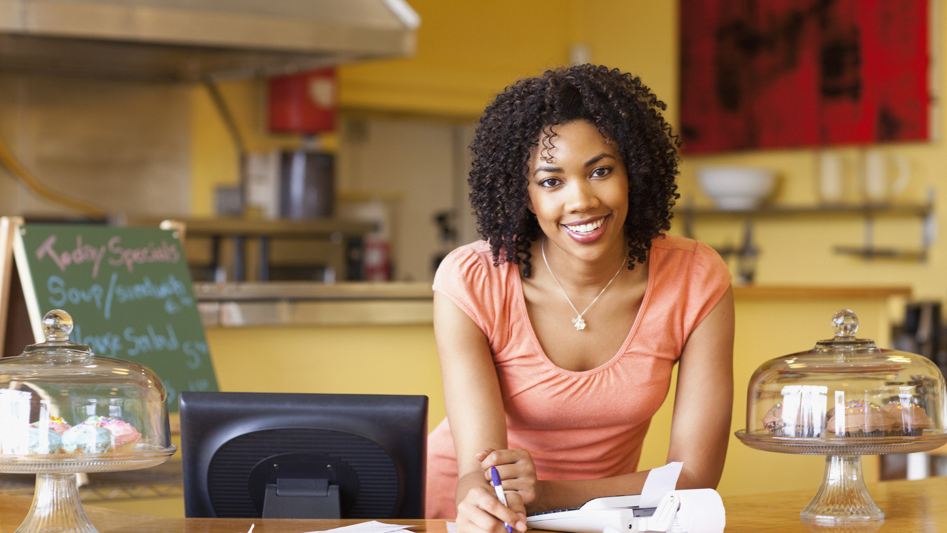 African American business owner paying bills at cafe counter