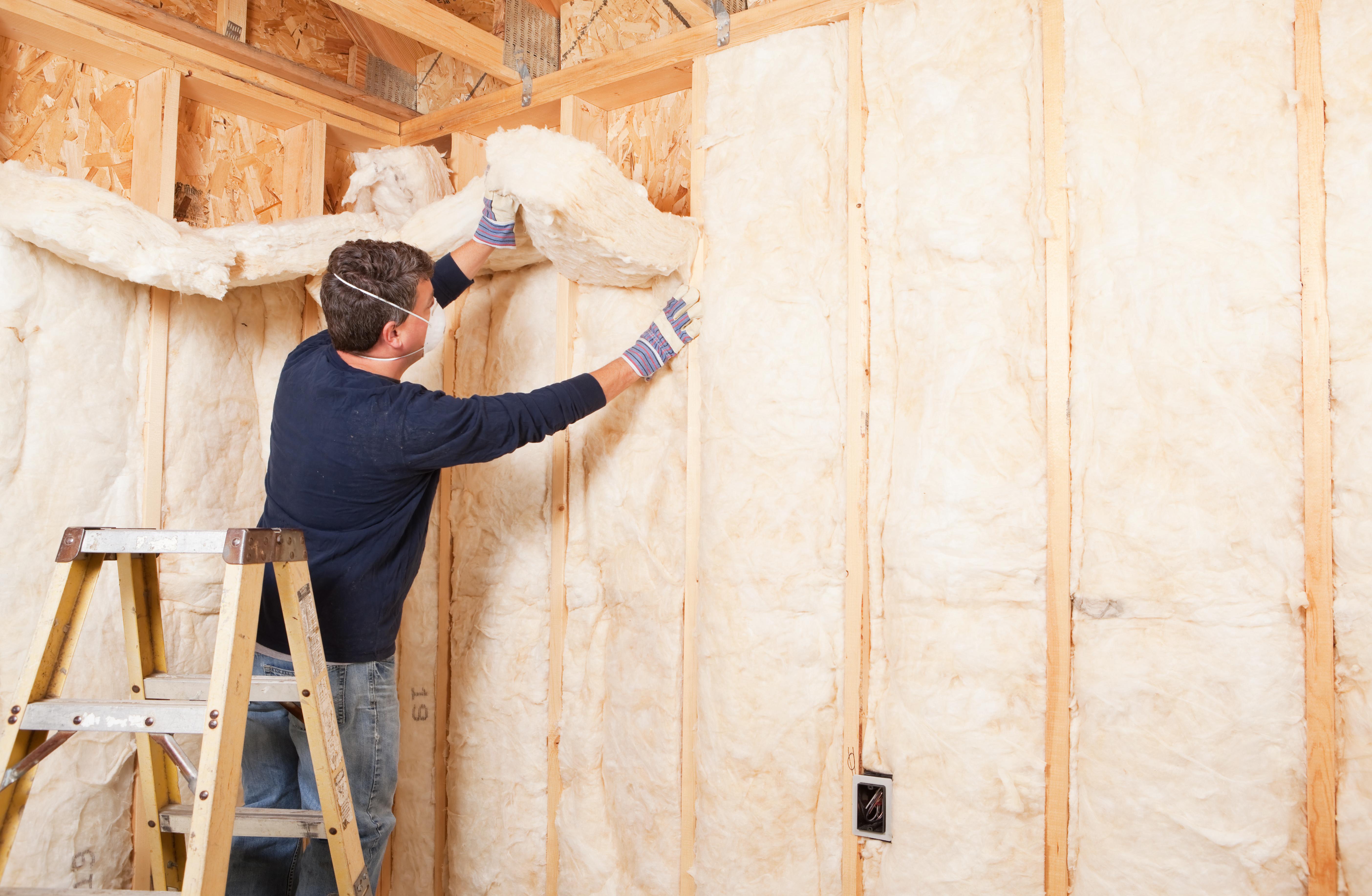 Construction Worker Insulating Wall with Fiberglass Batt
