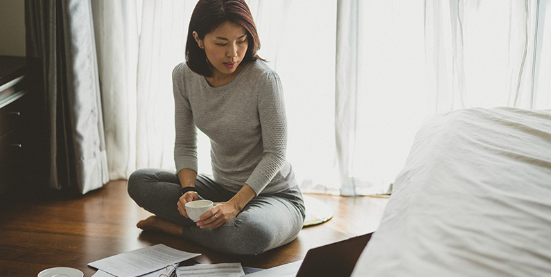 Custom Content - An Asian woman sitting on floor at home working with laptop and documents