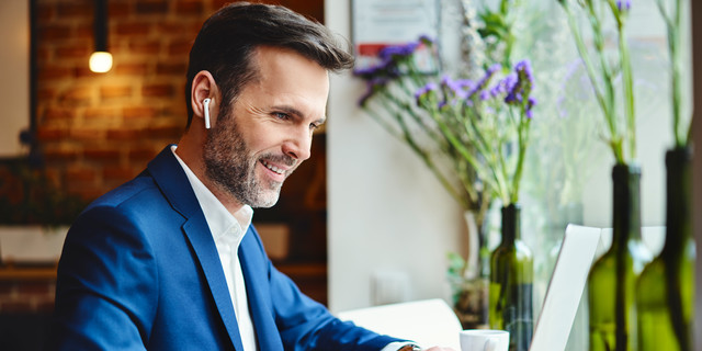 Happy businessman talking through wireless headphones while working on laptop in cafe