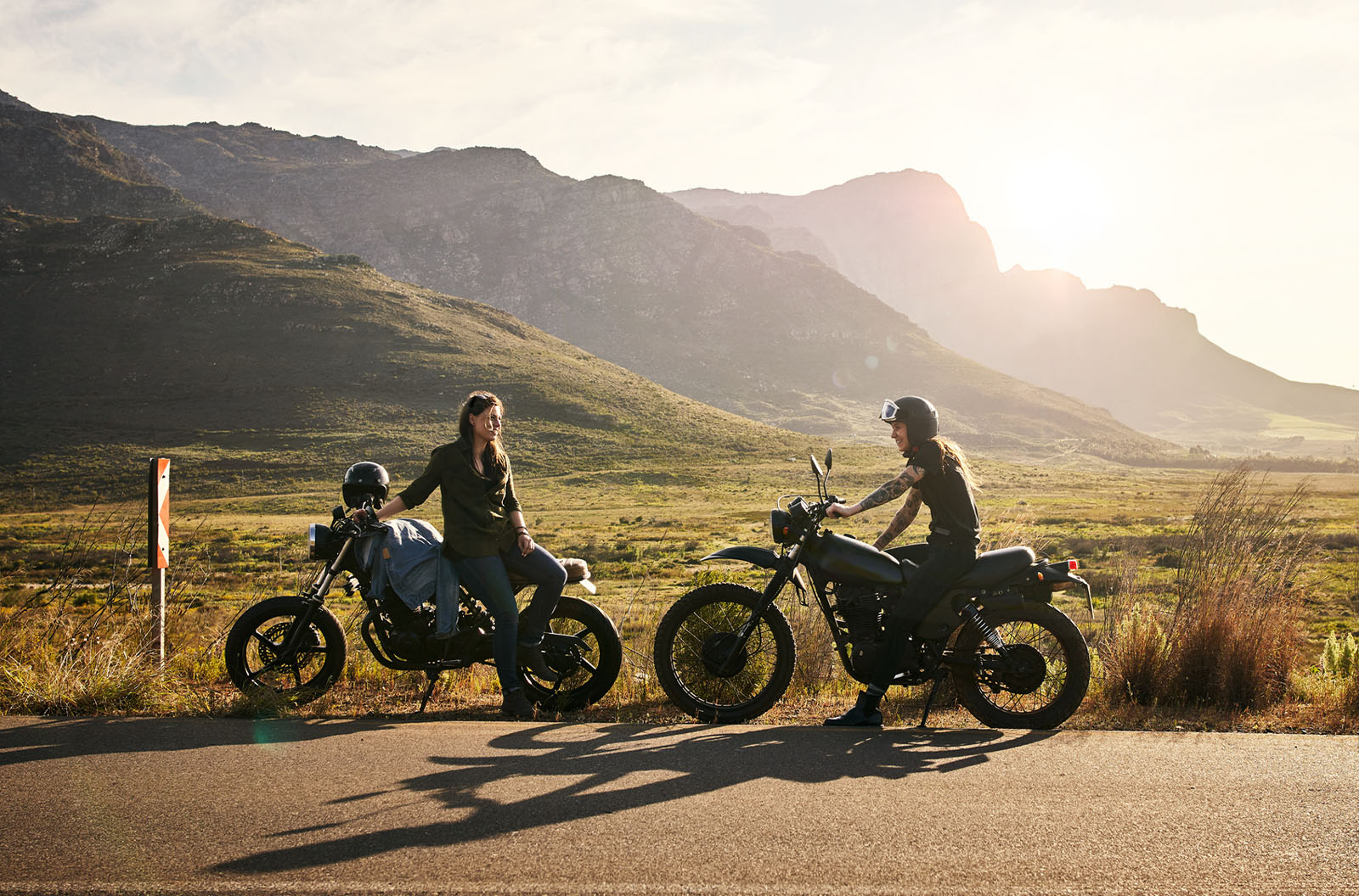 Two people resting on their motorcycles during a road trip