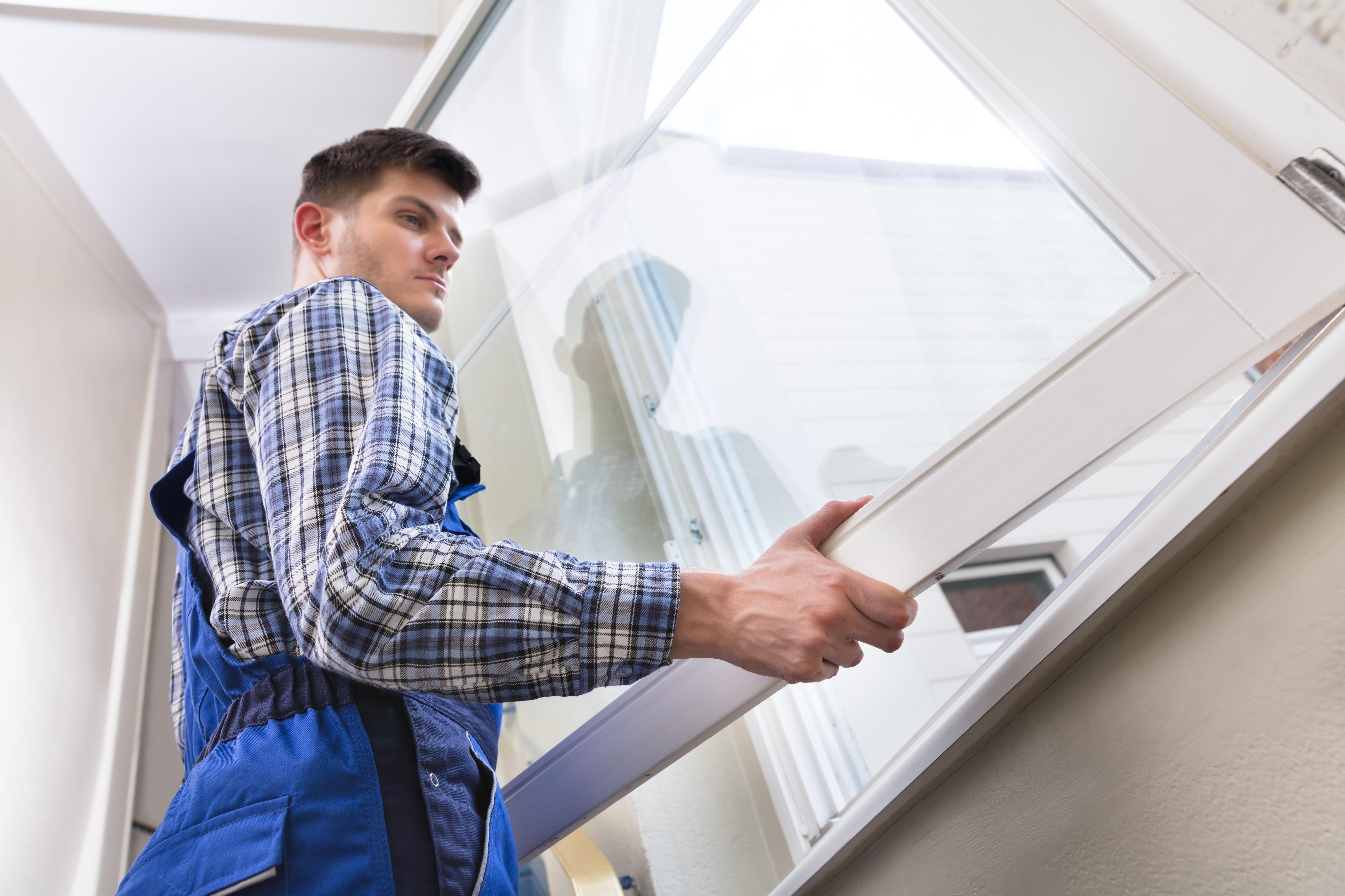 Male Repairman Installing Window