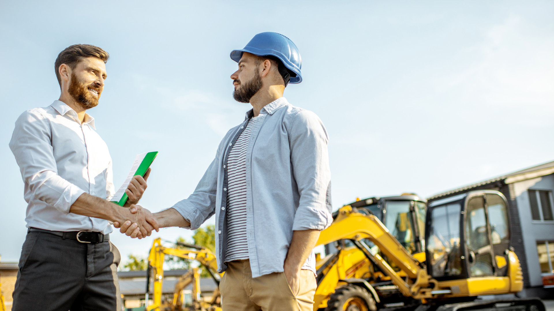 Builder with a sales consultant at the shop with heavy machinery