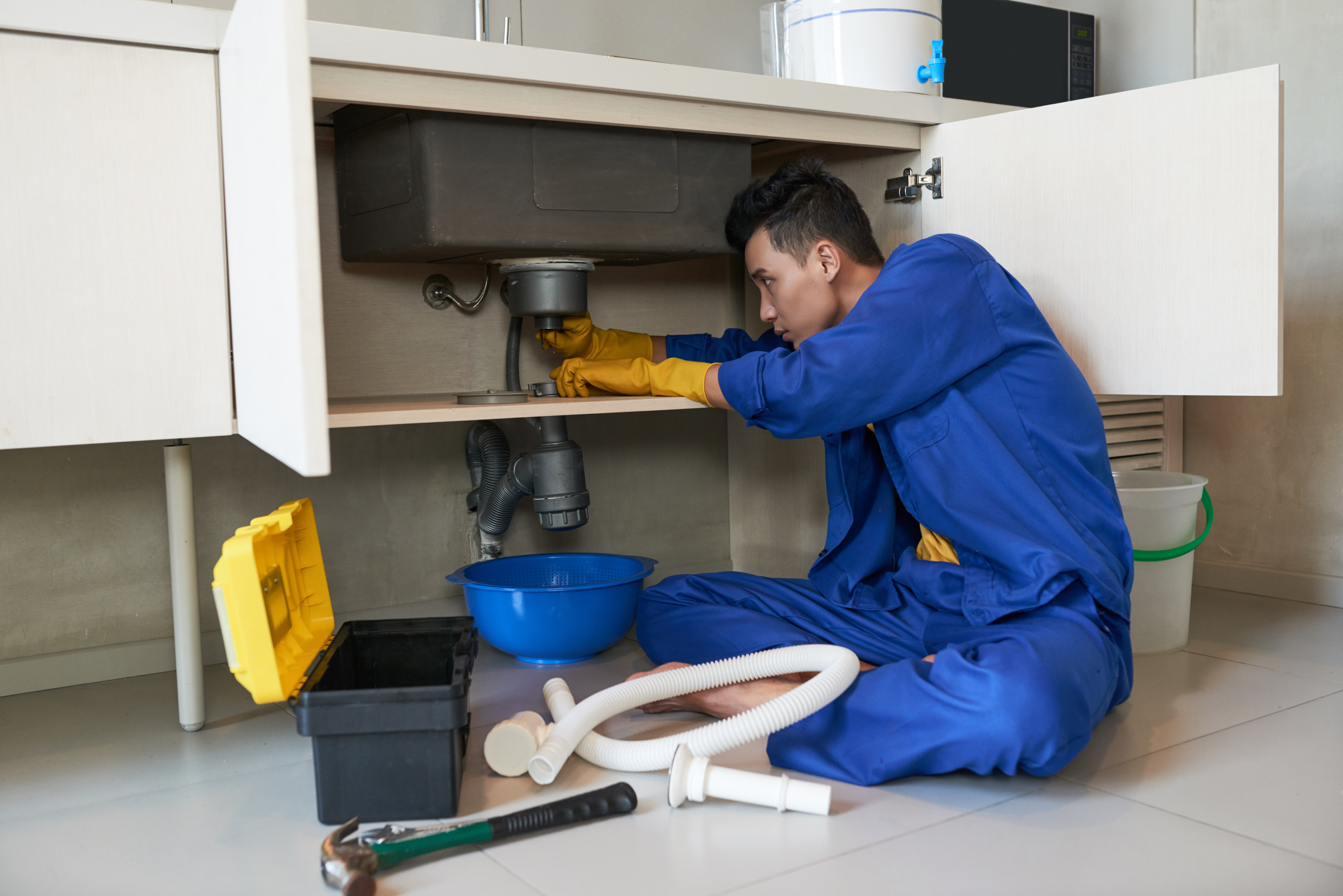 asian-plumber-blue-overalls-clearing-blockage-drain.jpg