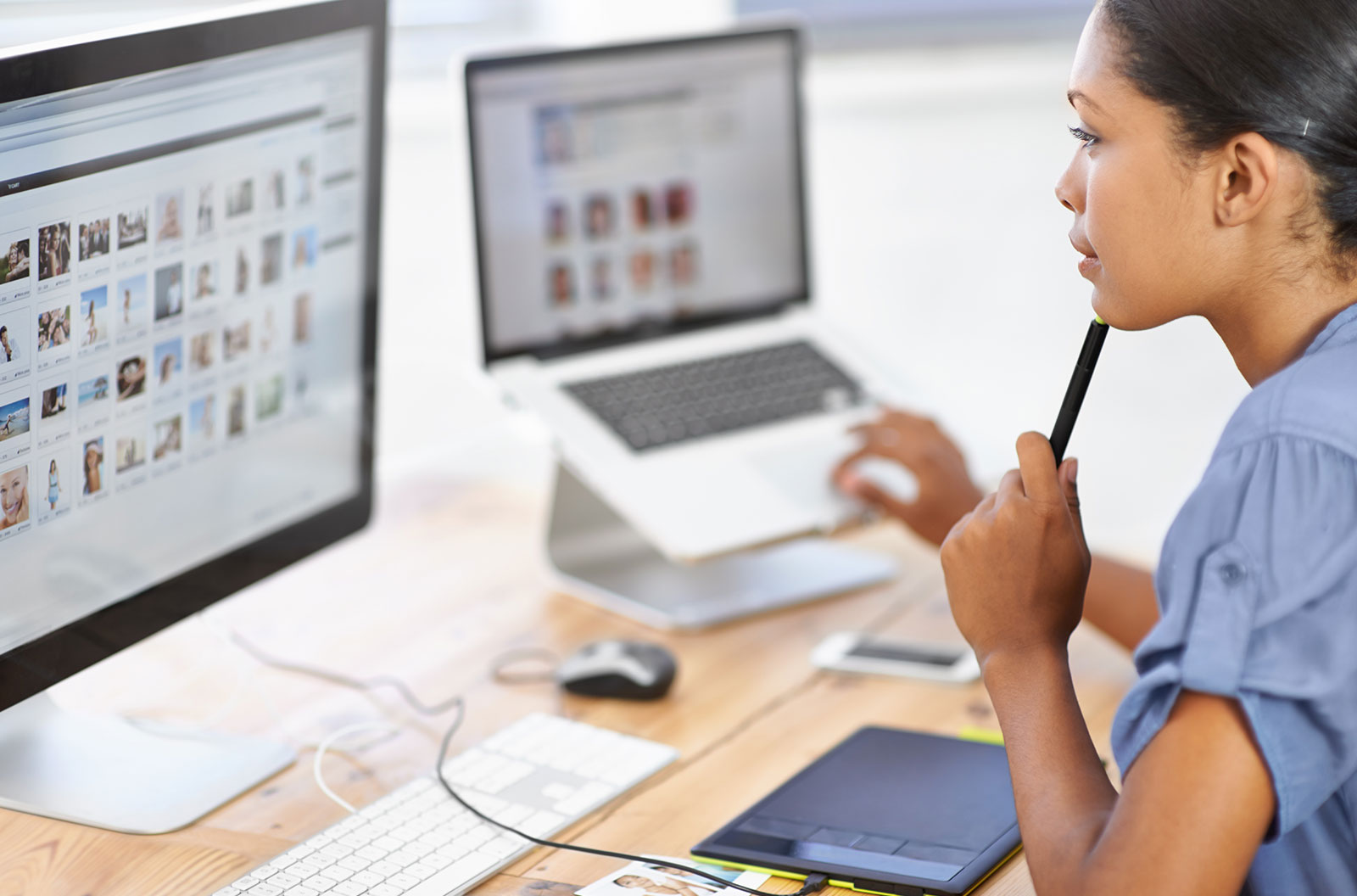 Young female editor in front of her computer pondering what stock images to use in her project