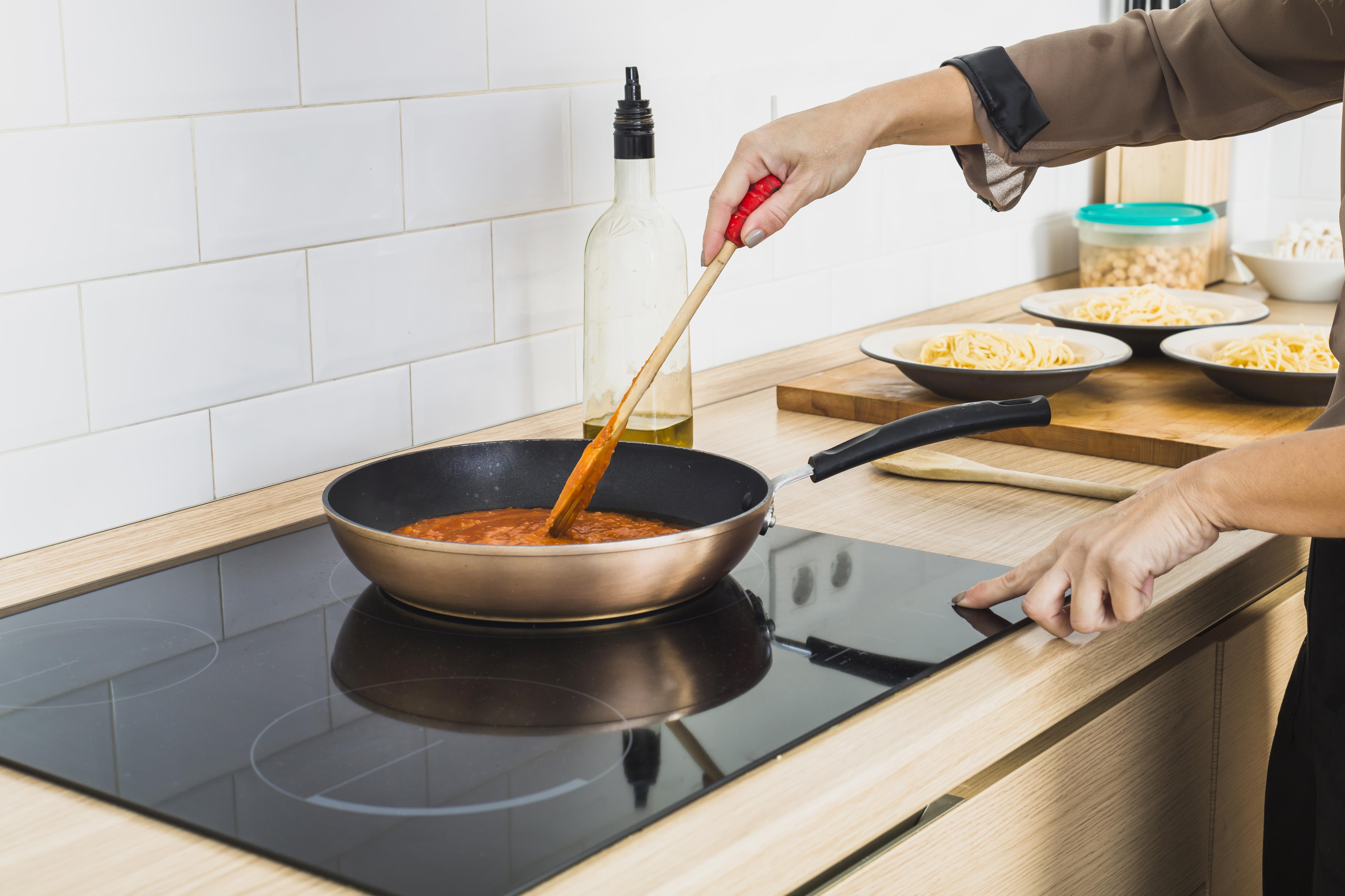 person-mixing-sauce-pan-stove.jpg