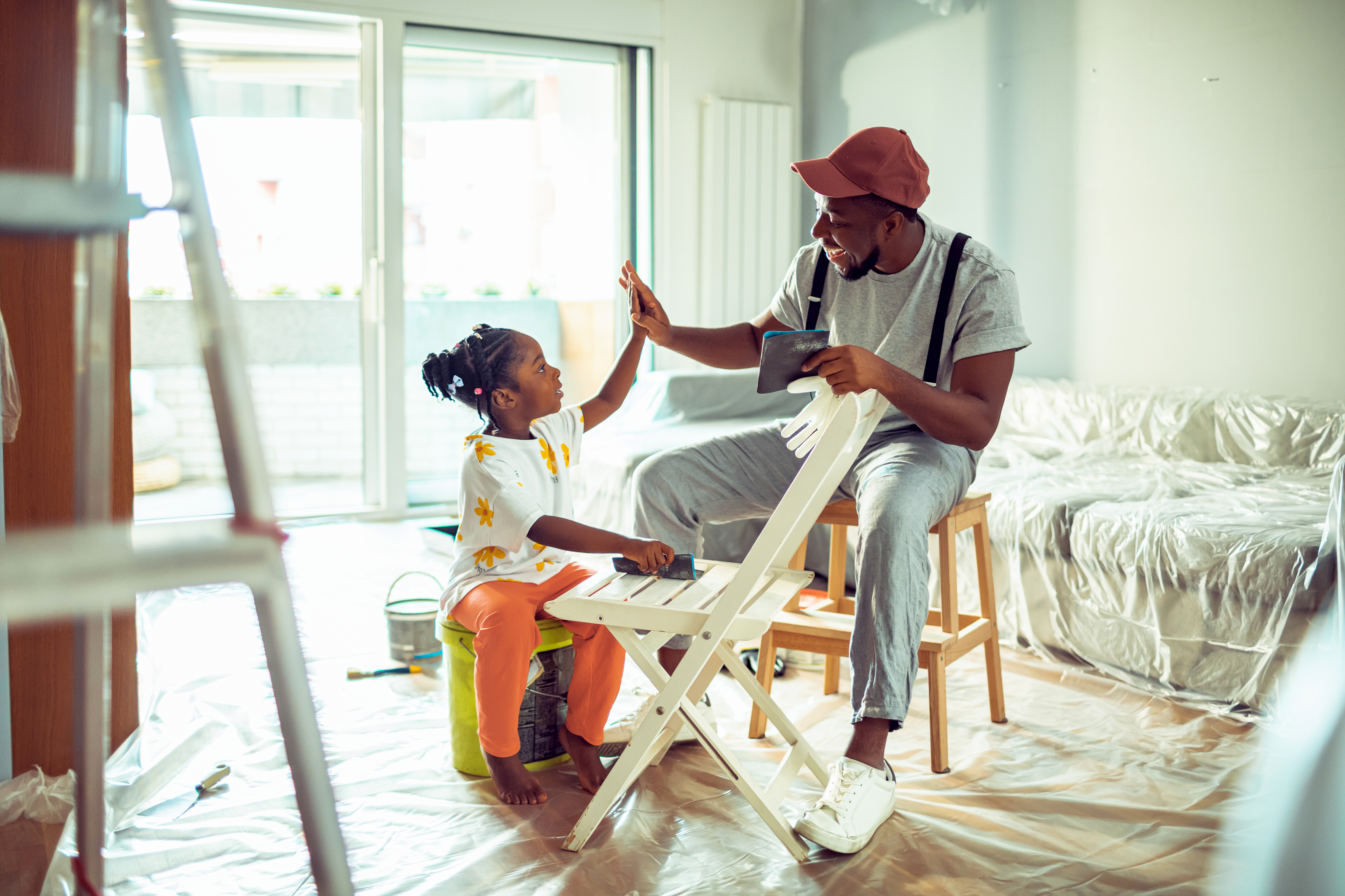 Father painting a chair with his daughter