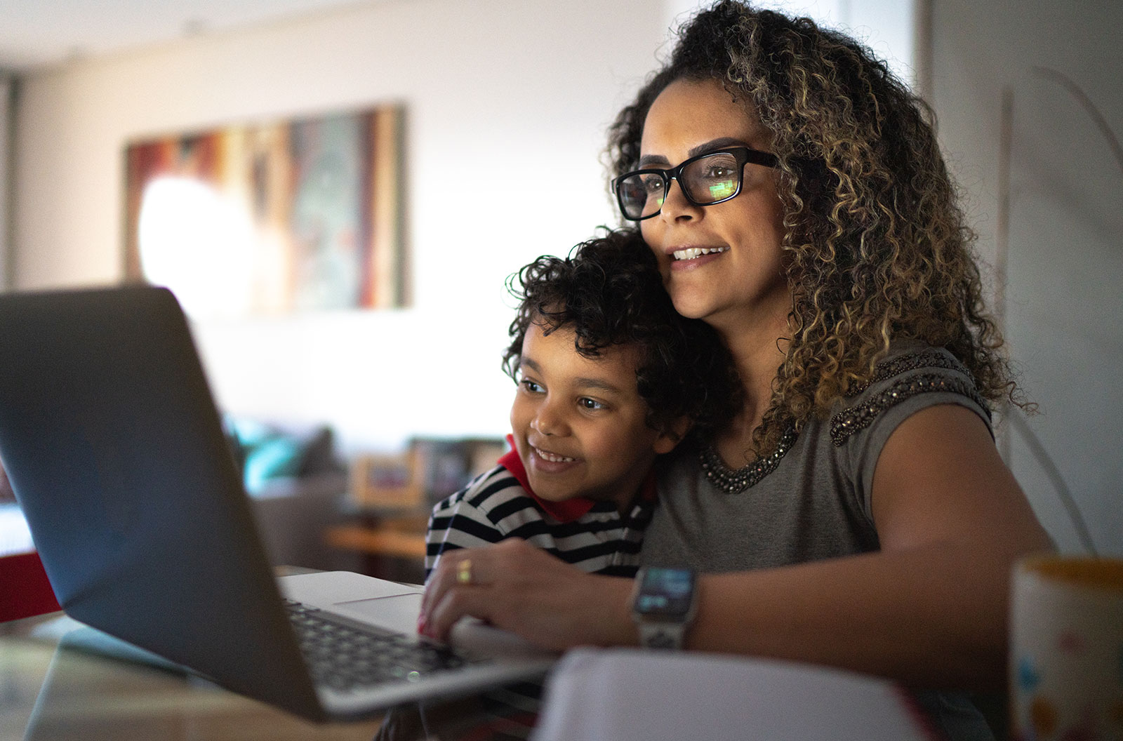 Curly-haired woman working on her laptop at home with her son