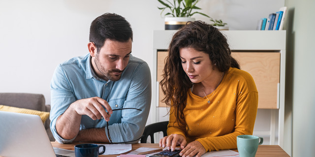 Young couple calculating their domestic bills at home stock photo