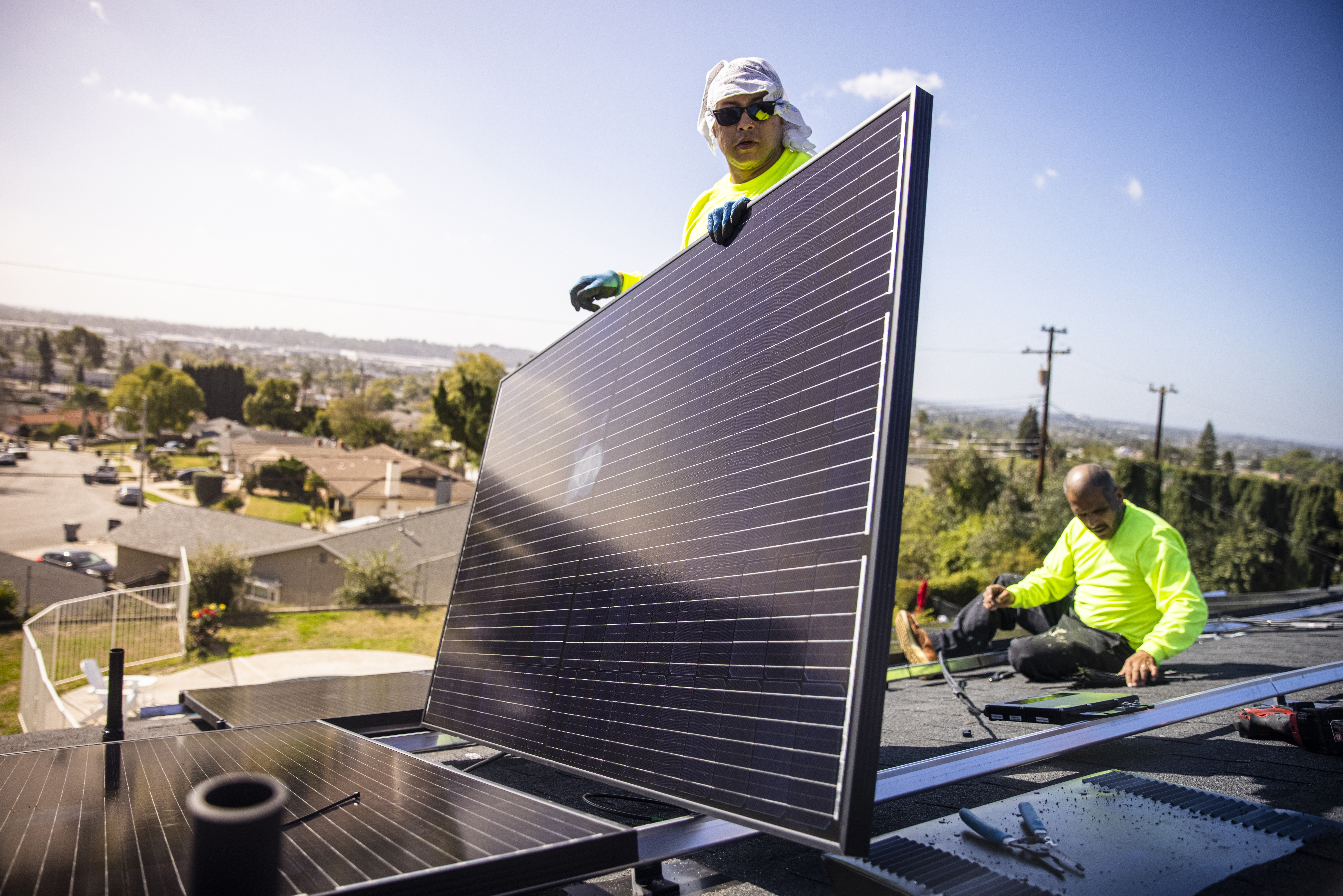 Team of Workers Installing Solar Panels on Residential Rooftop in California
