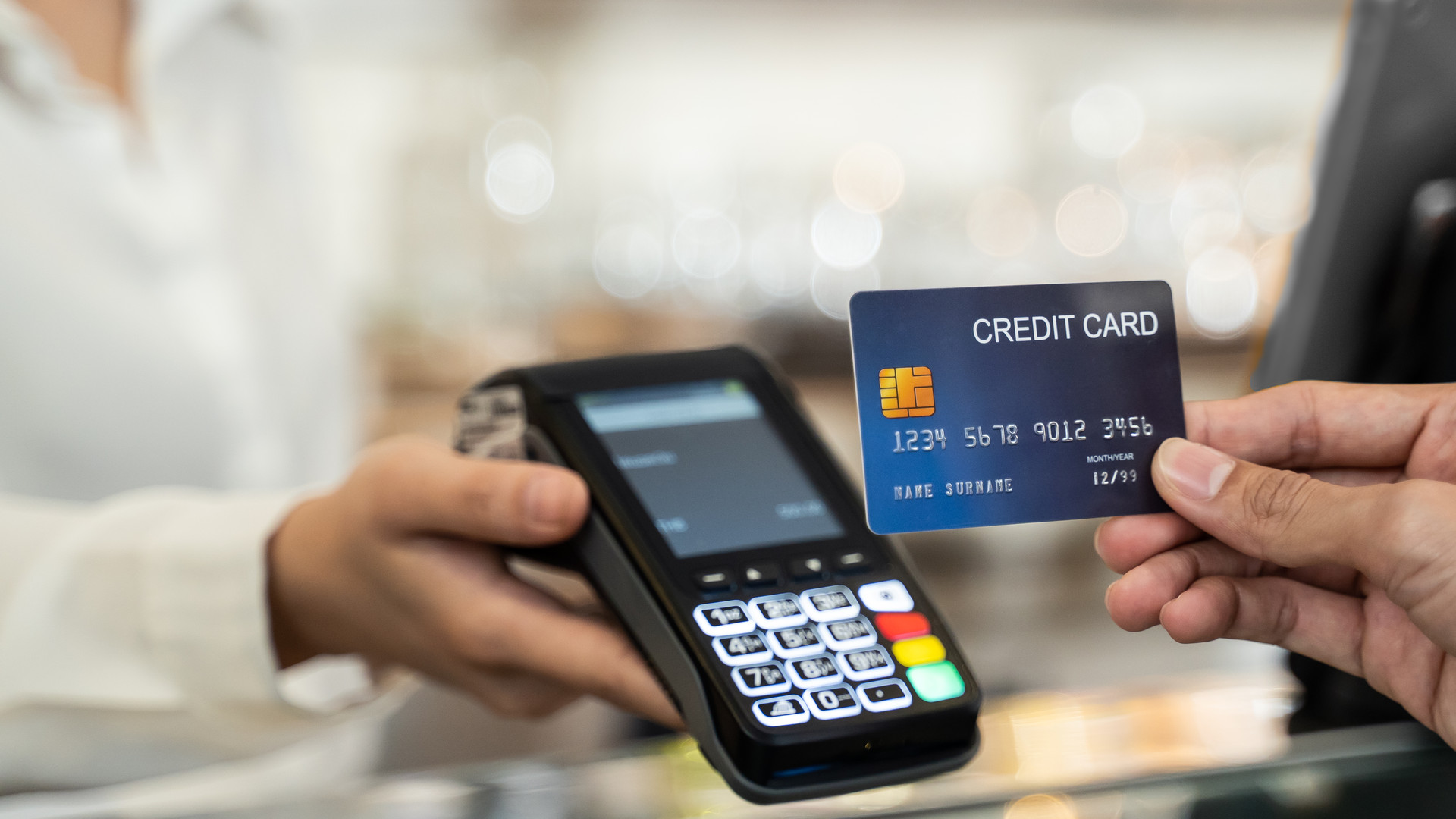 Close up shot of customer hand using dummy credit card for payment to waitress at cashier in cafe restaurant, money cashless and credit card payment technology concept.