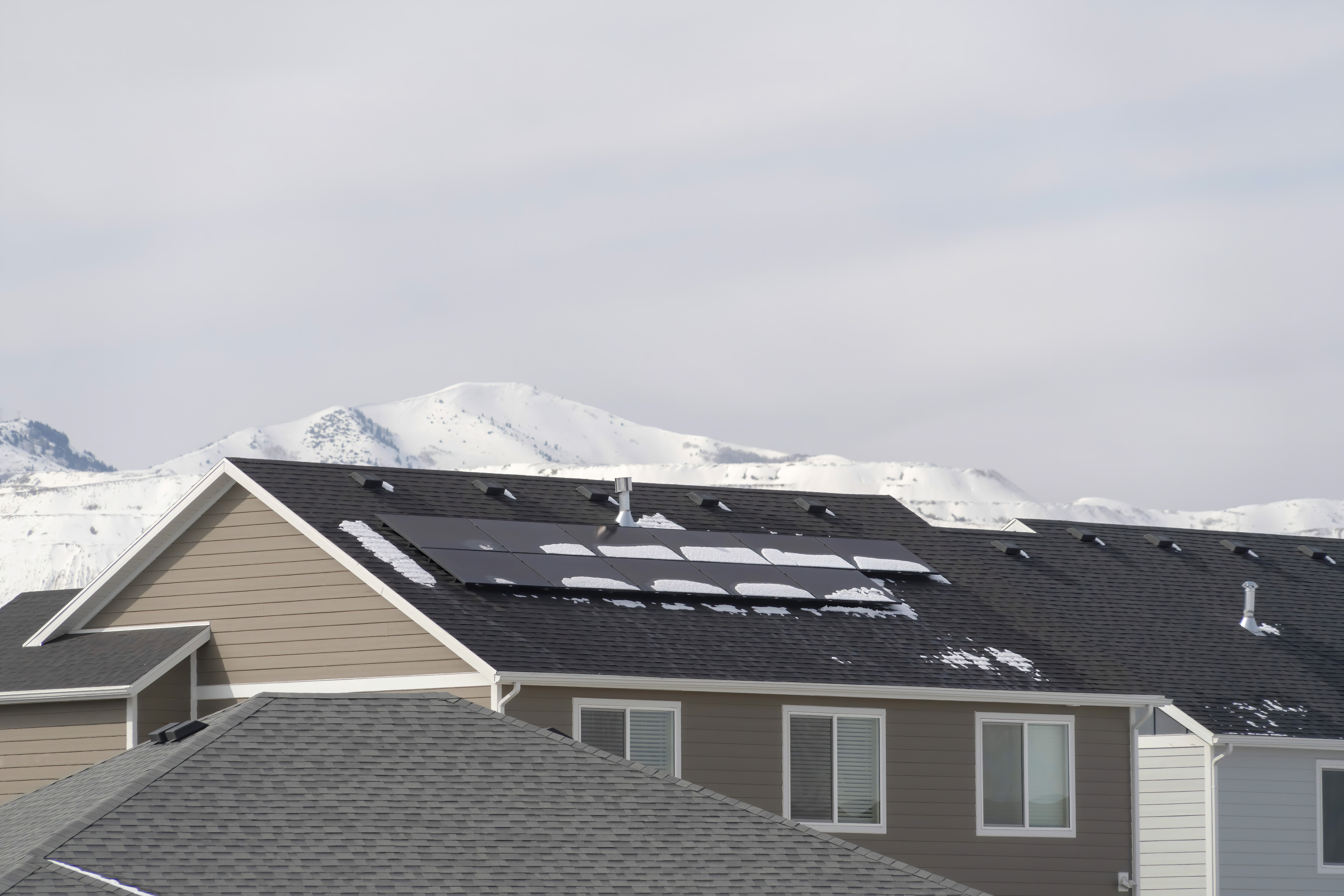 Exterior of homes with solar panels on gray roof against snowy Wasatch Mountain