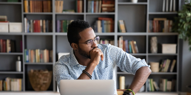 African businessman sitting at workplace thinking over problem solution