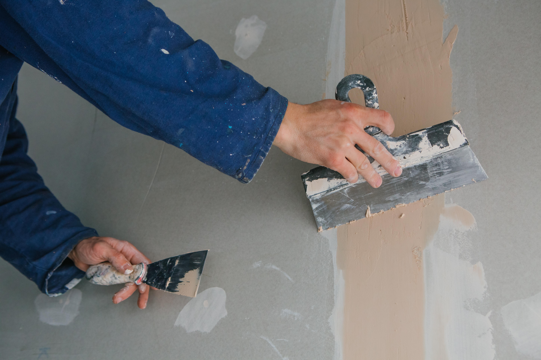 plasterer-man-works-plastering-two-trowels-plasterboard-blue-uniform.jpg