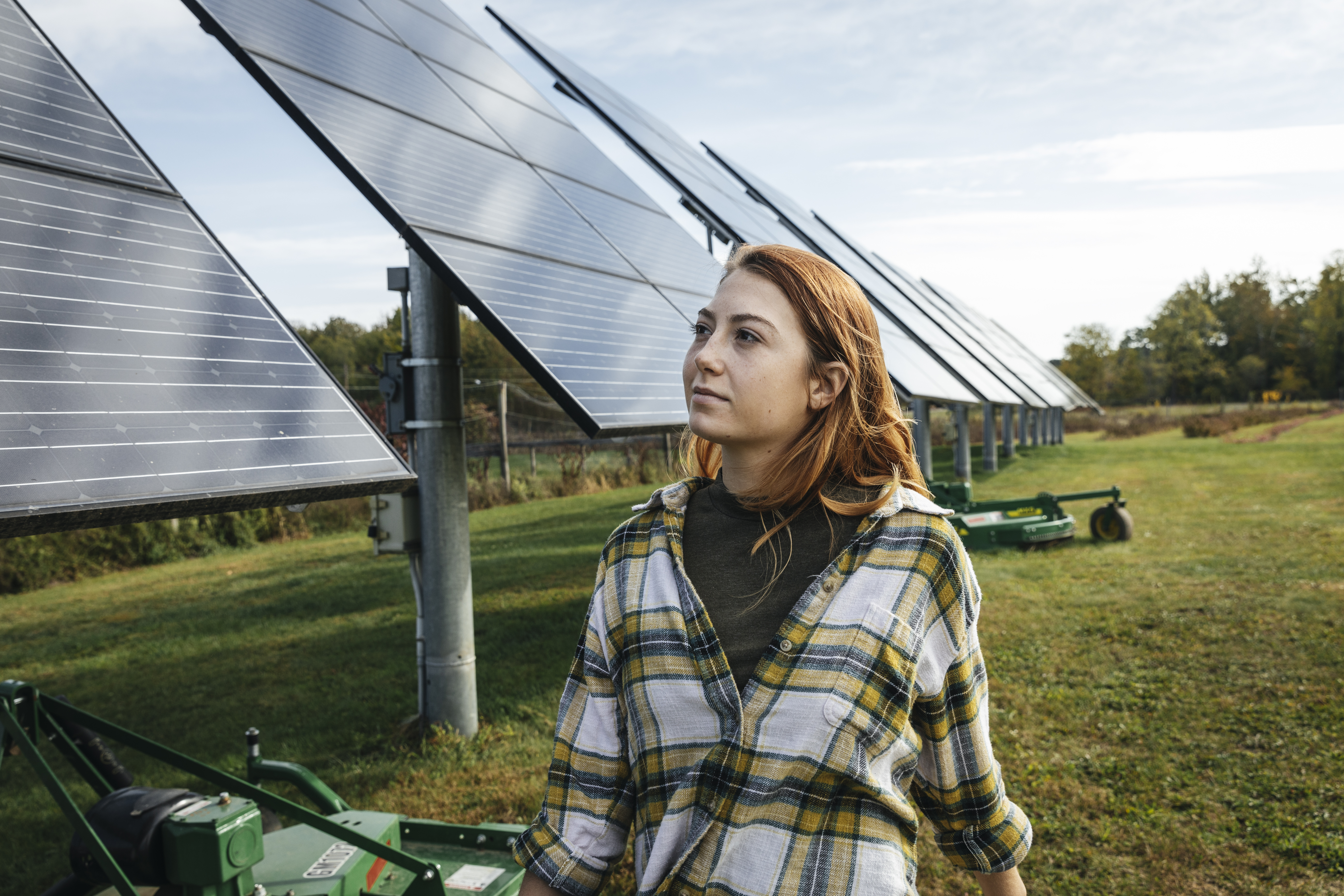 Young woman looking at solar panels on farm