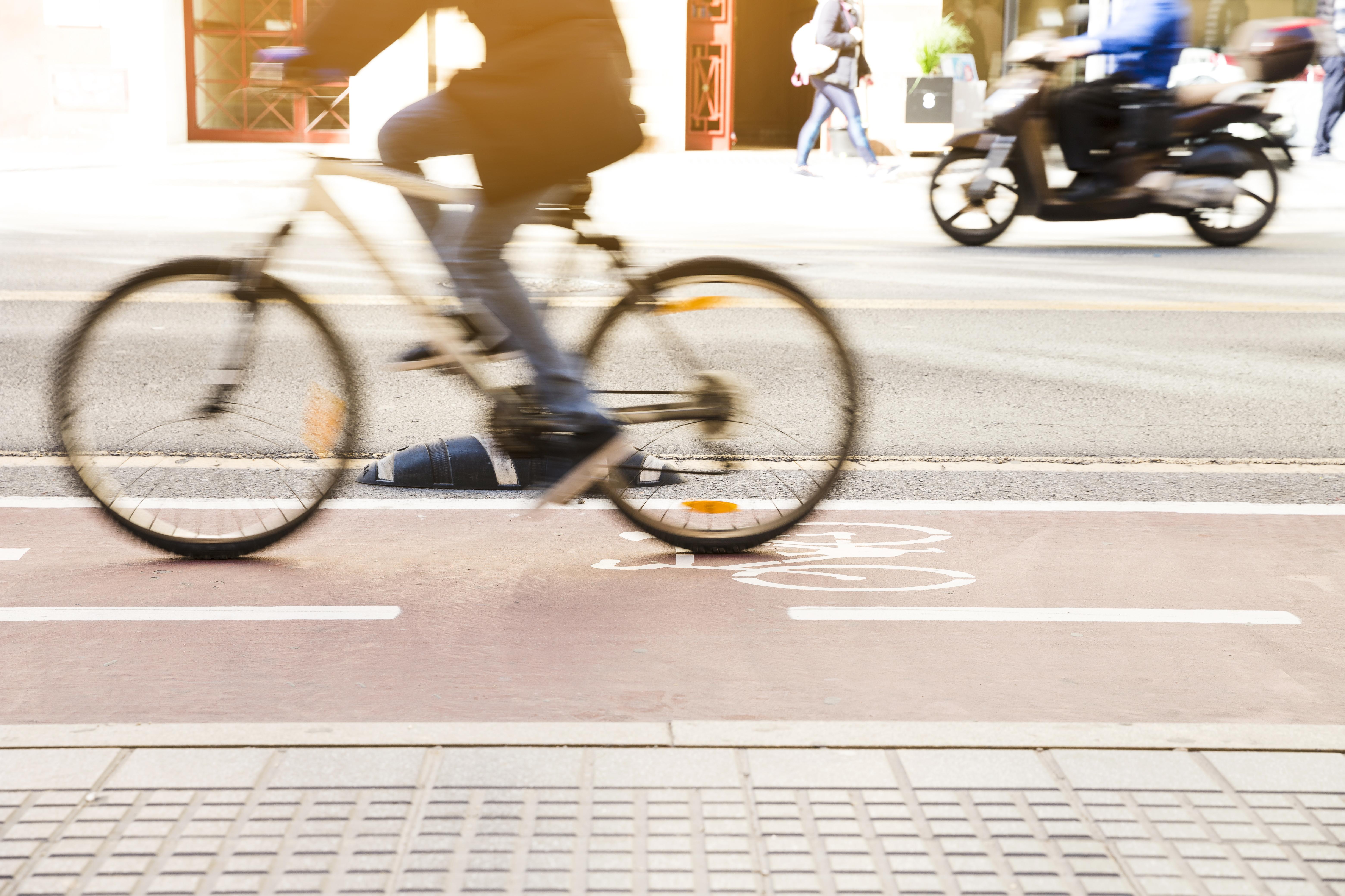 unrecognizable-cyclist-riding-bike-bicycle-lane-through-city-street.jpg