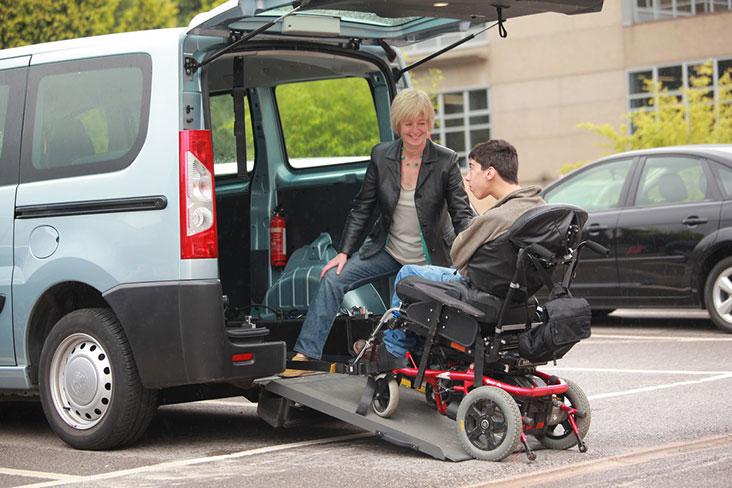 Man in wheelchair boarding Wheelchair Accessible Vehicle (WAV) using a ramp