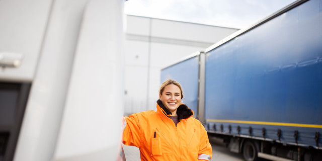 Female transport engineer standing by the truck outdoors
