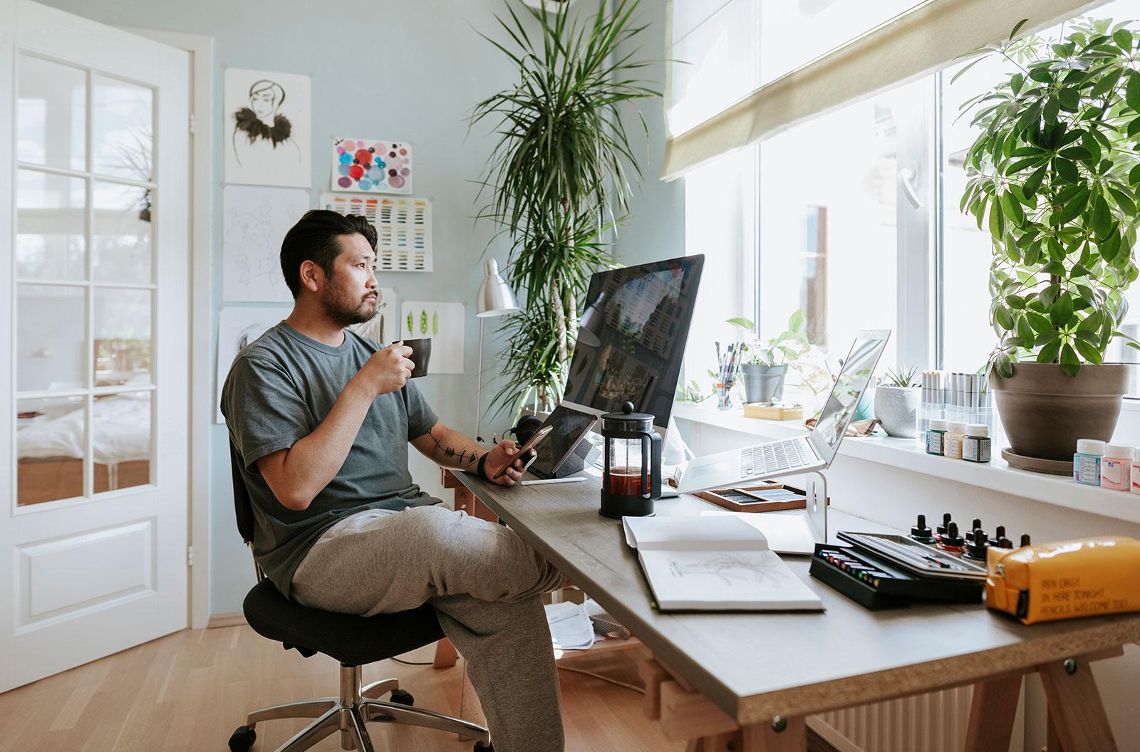 Digital artist contemplates during a coffee break in his home studio