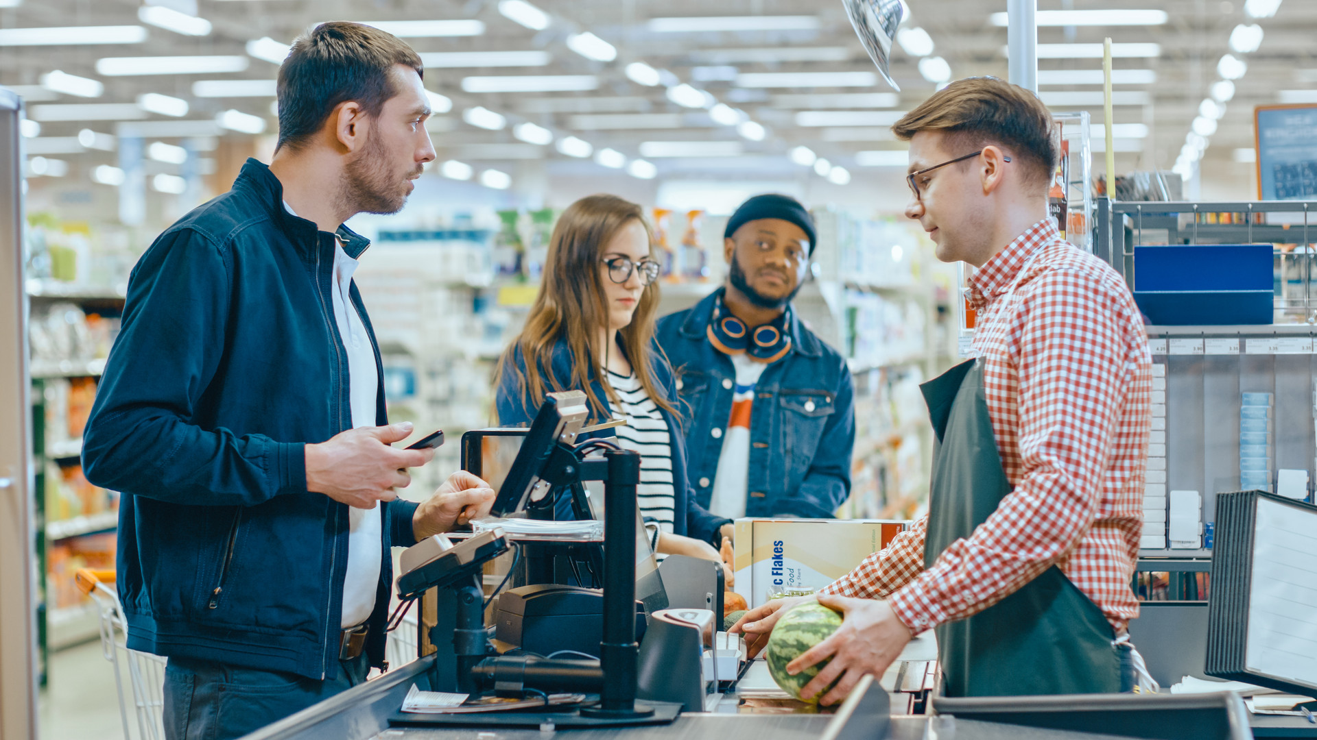 At the Supermarket: Checkout Counter Customer Pays with Smartphone for His Items. Big Shopping Mall with Friendly Cashier, Small Lines and Modern Wireless Paying Terminal System.