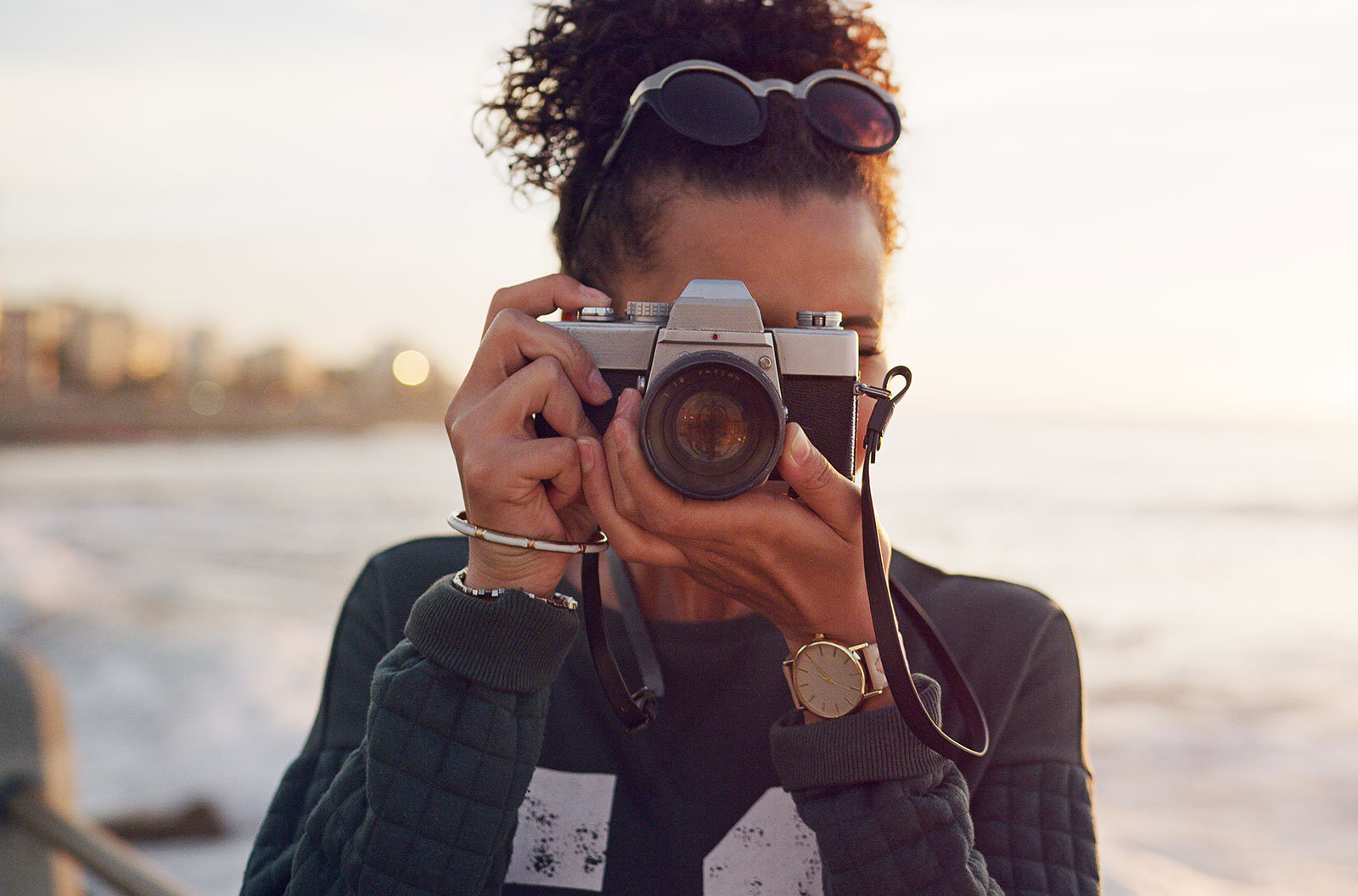 Young woman standing alone in the city and taking a picture with her camera