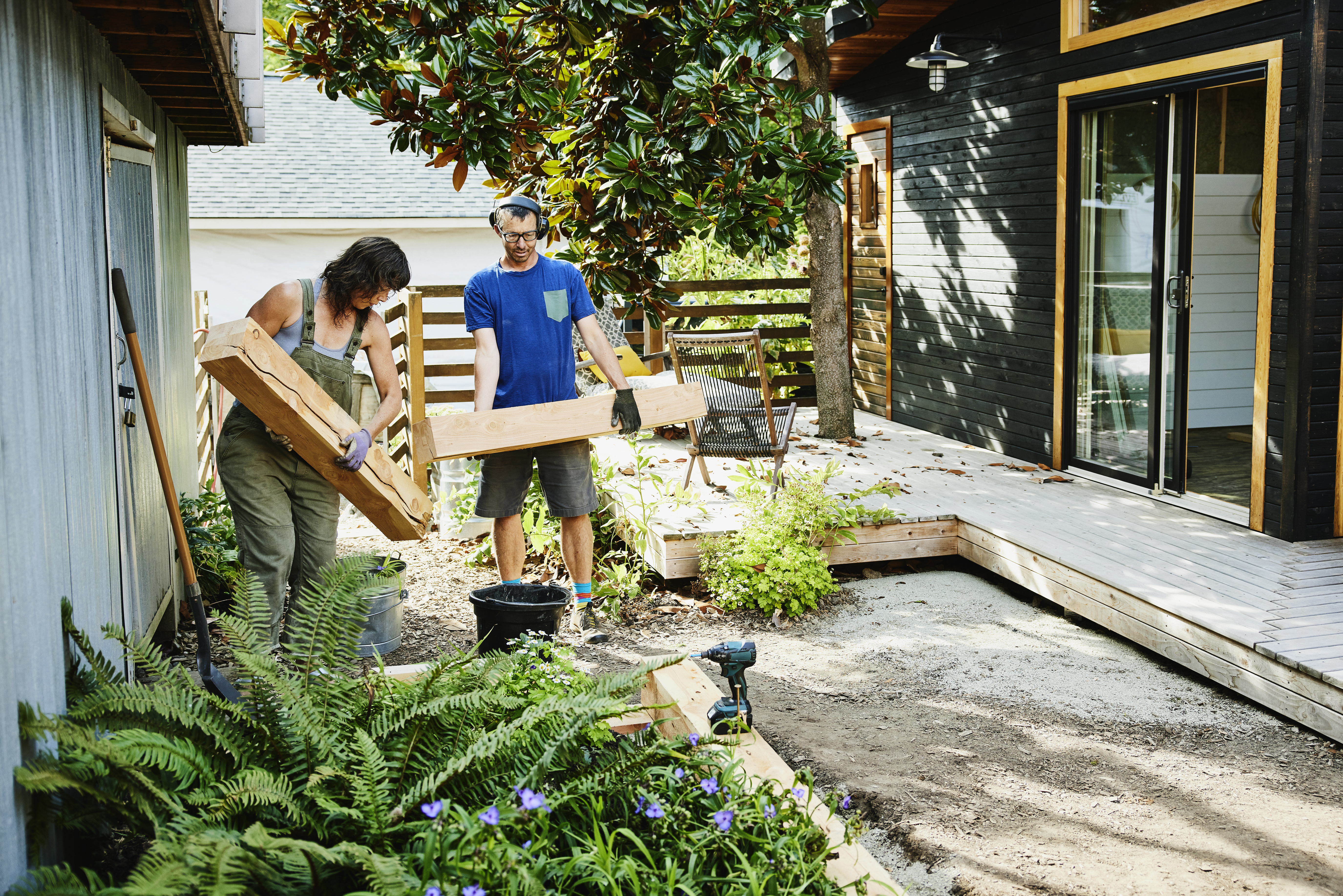 Couple carrying lumber to build raised garden beds in backyard