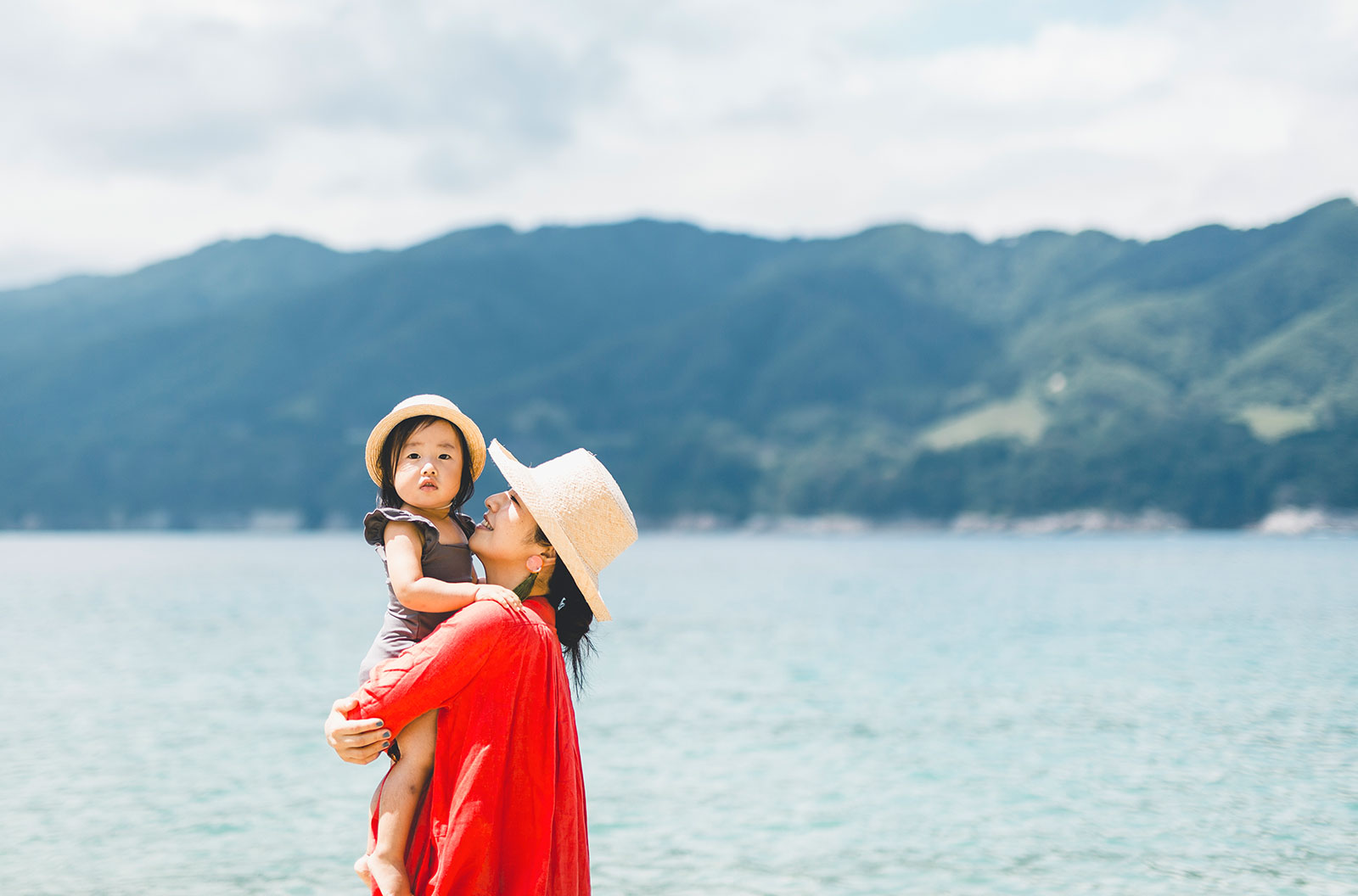 Mother holding and looking up a her young daughter while relaxing by the beach