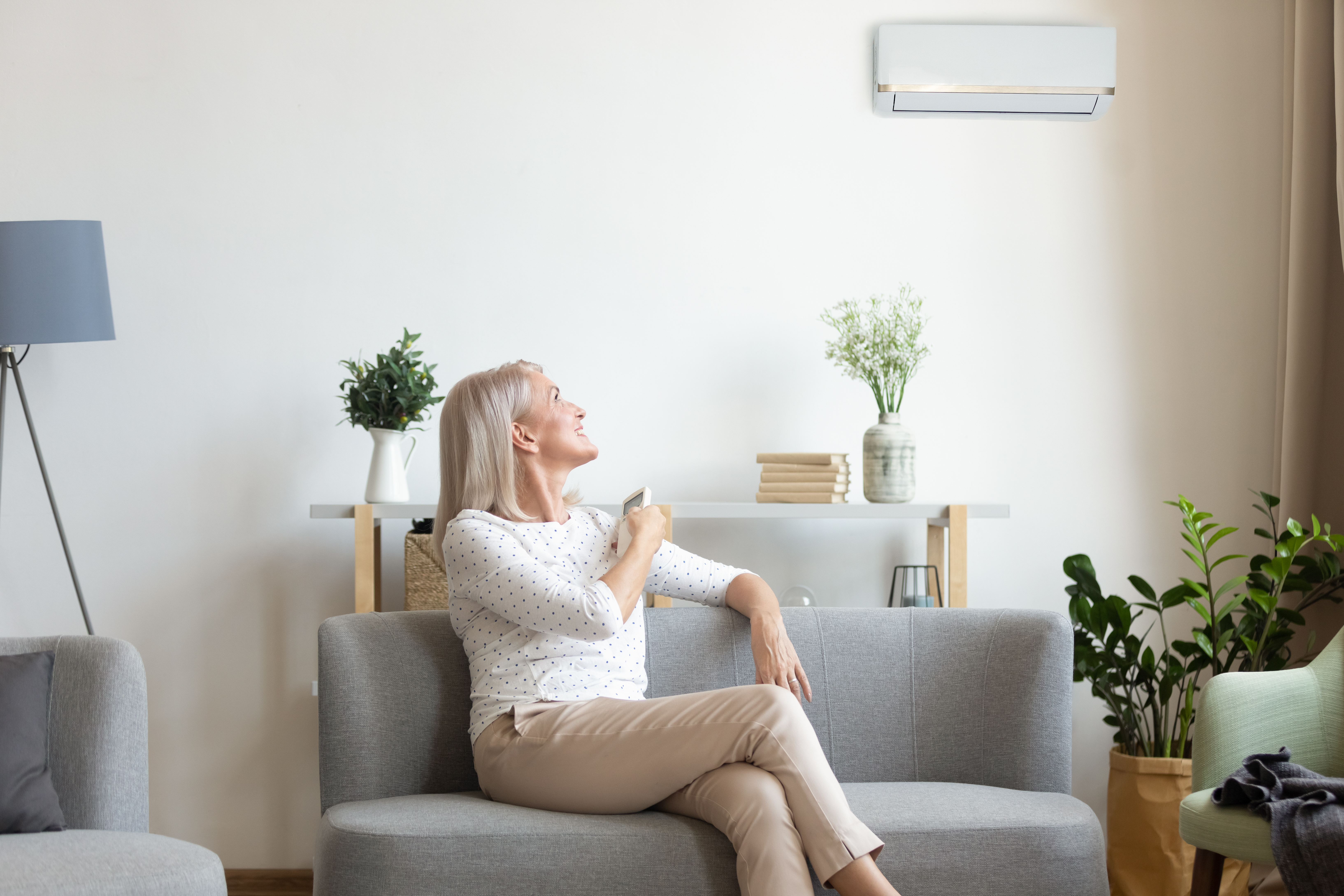 Middle aged woman switching on air conditioner in living room