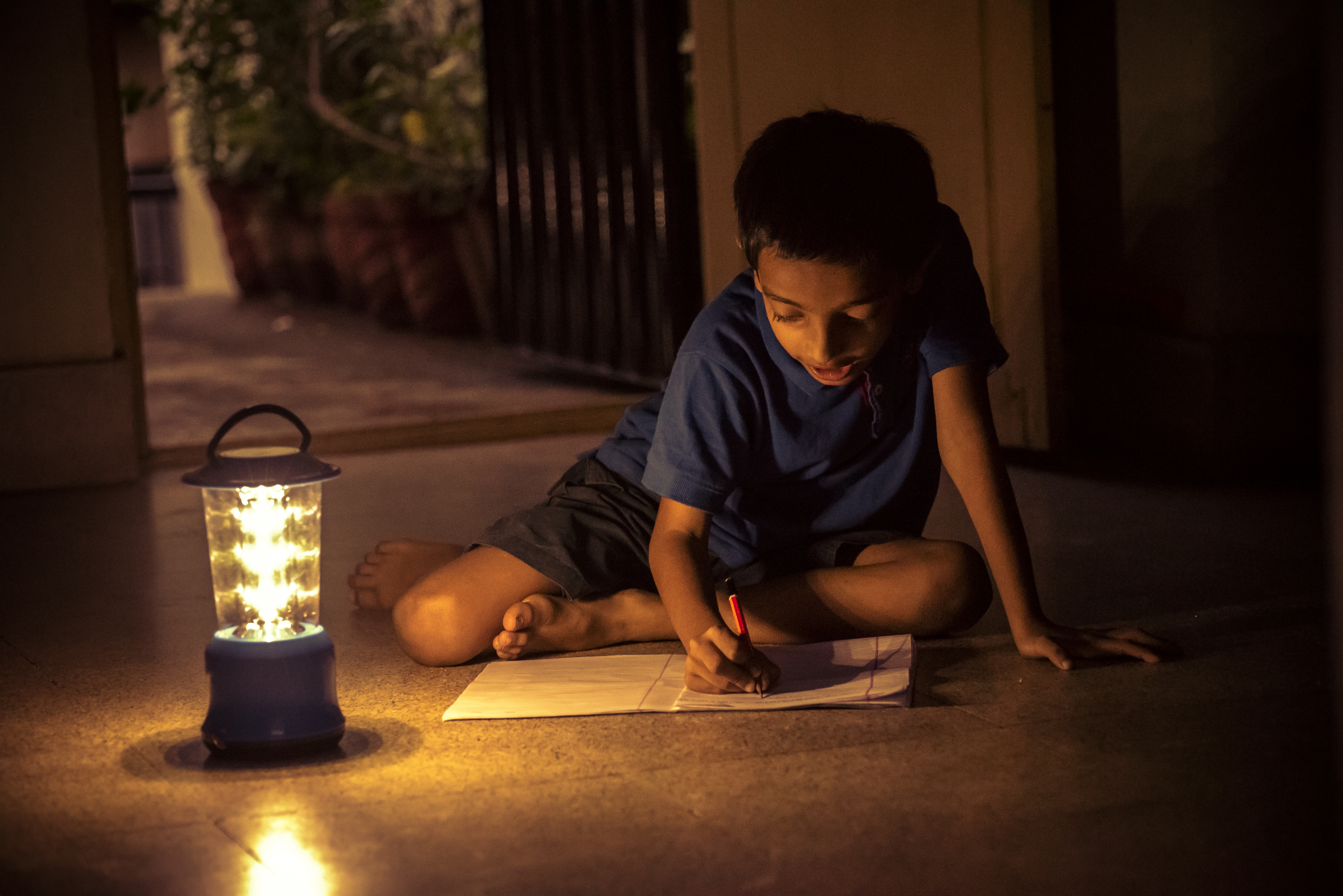 7 years Indian Boy studying under lamp