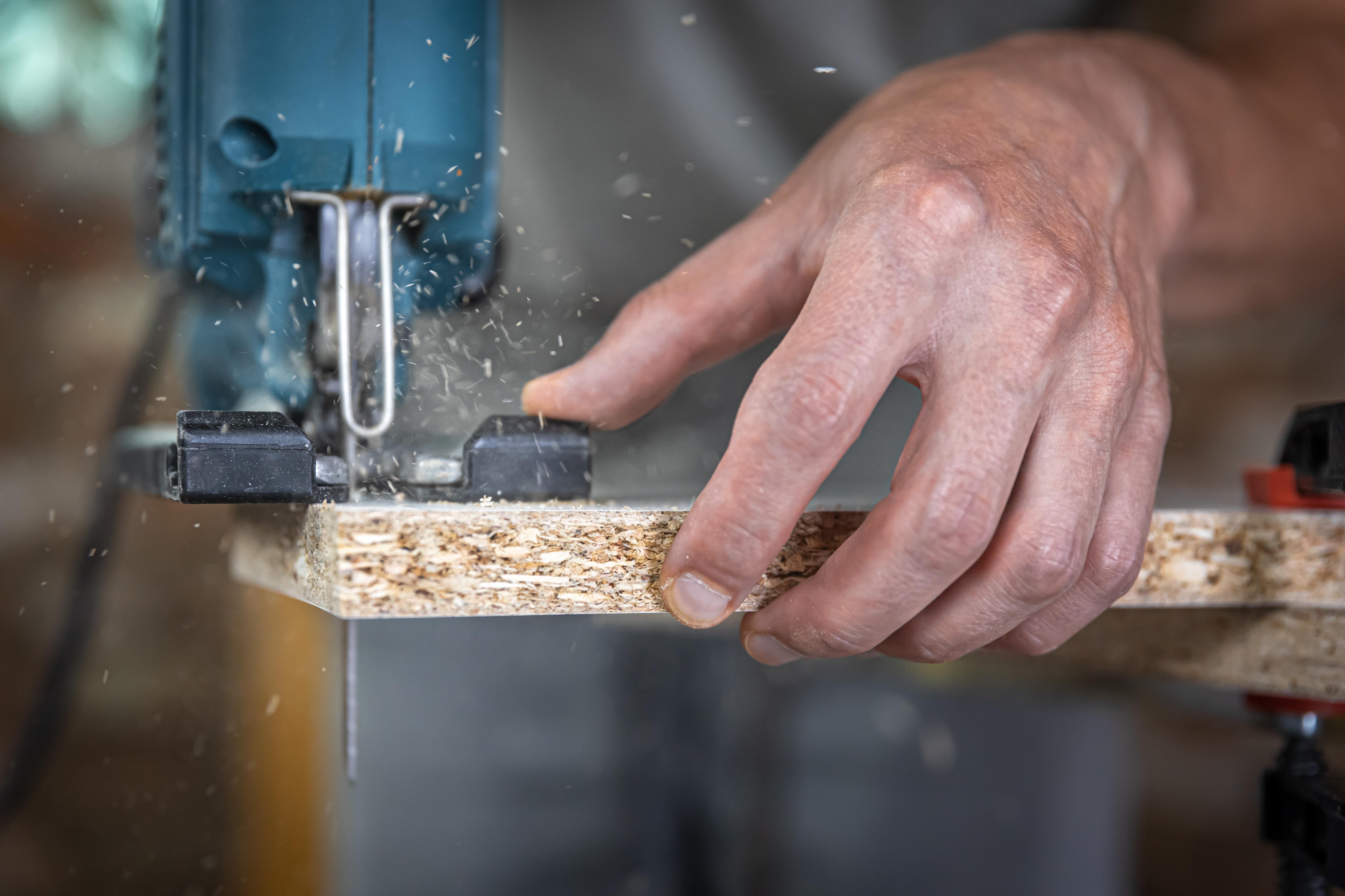 close-up-carpenter-s-hands-process-cutting-wood-with-jigsaw.jpg