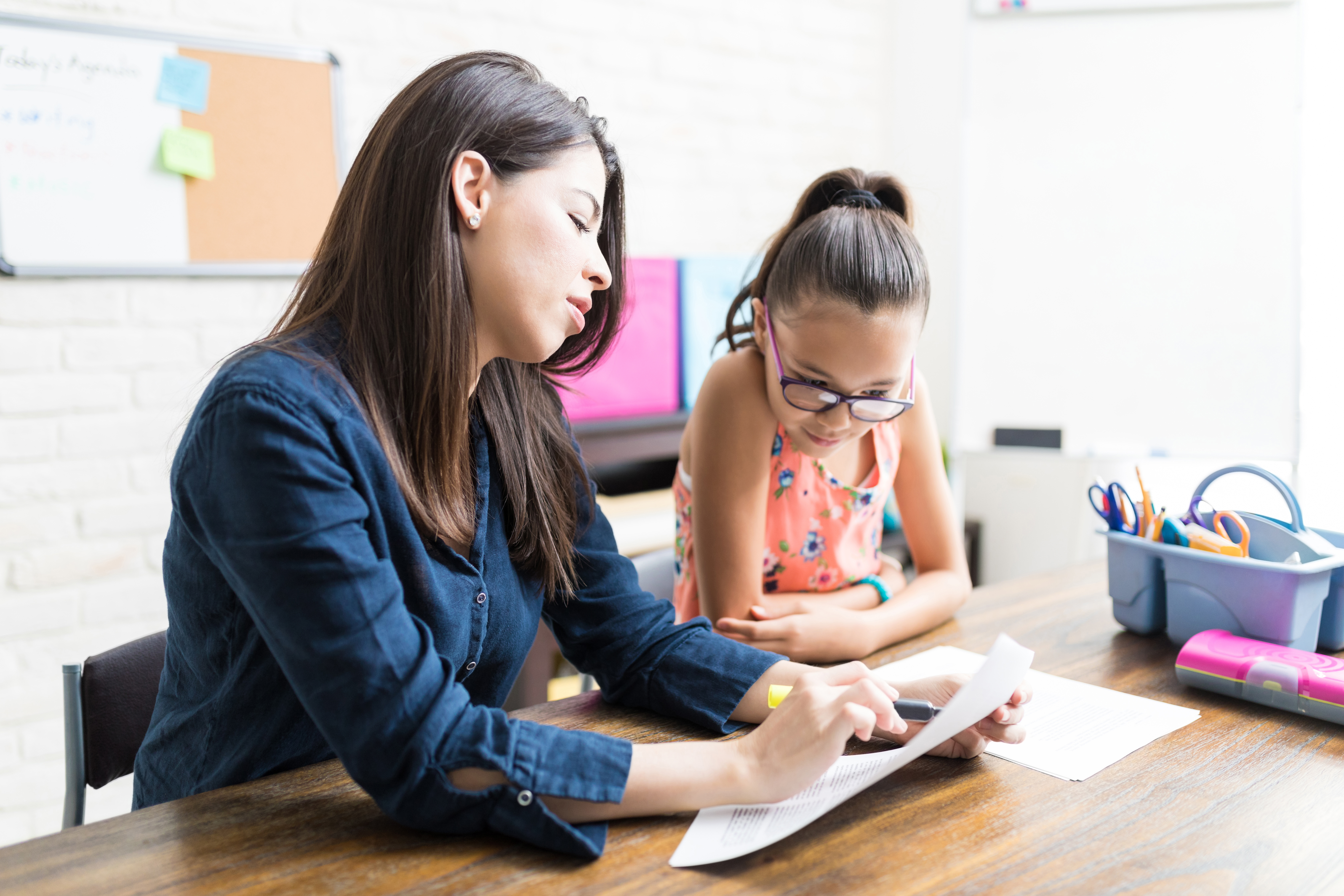 Mother Helping Girl With Homework At Table In House