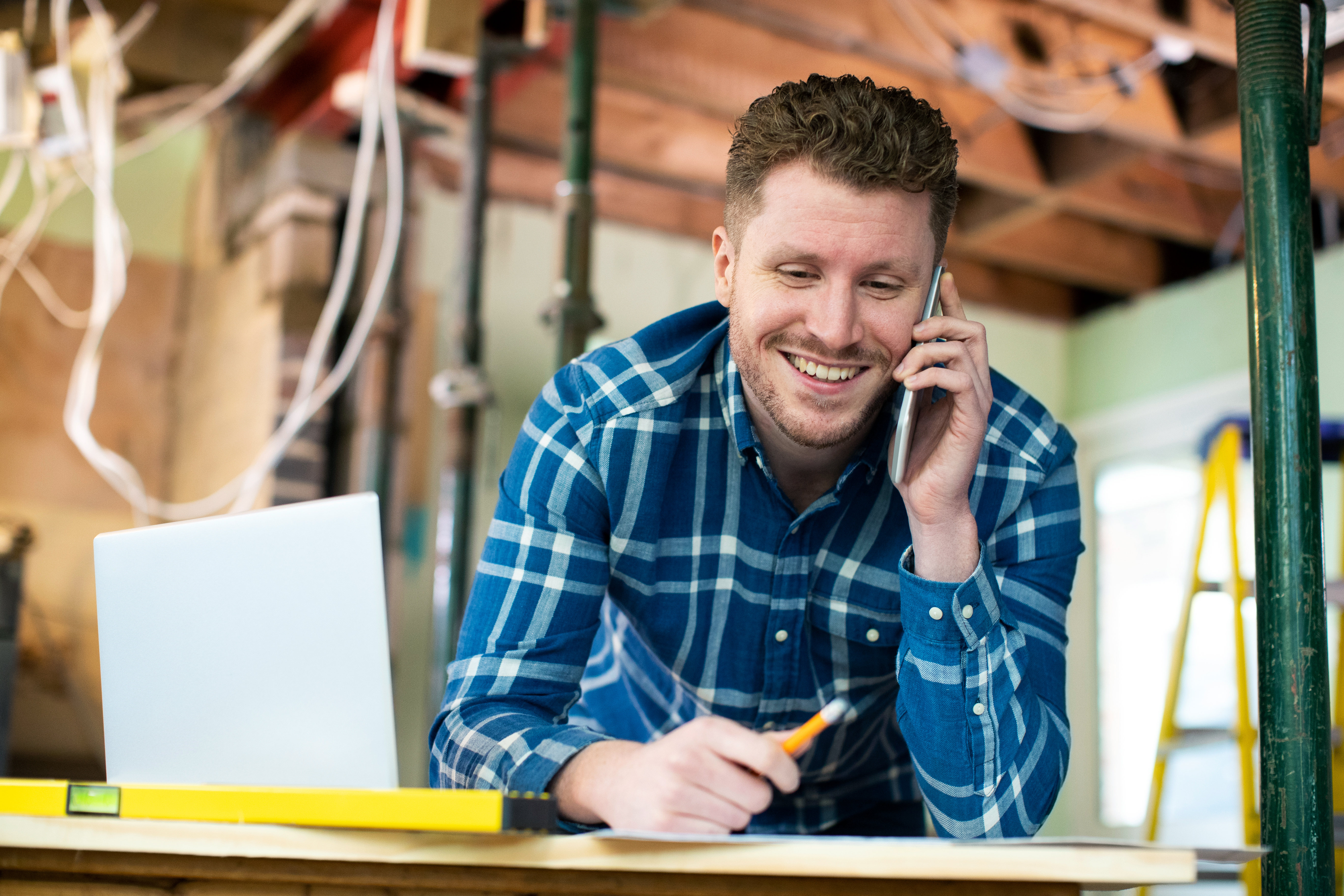 Architect Inside House Being Renovated Working On Plans Using Laptop And Talking On Cellphone
