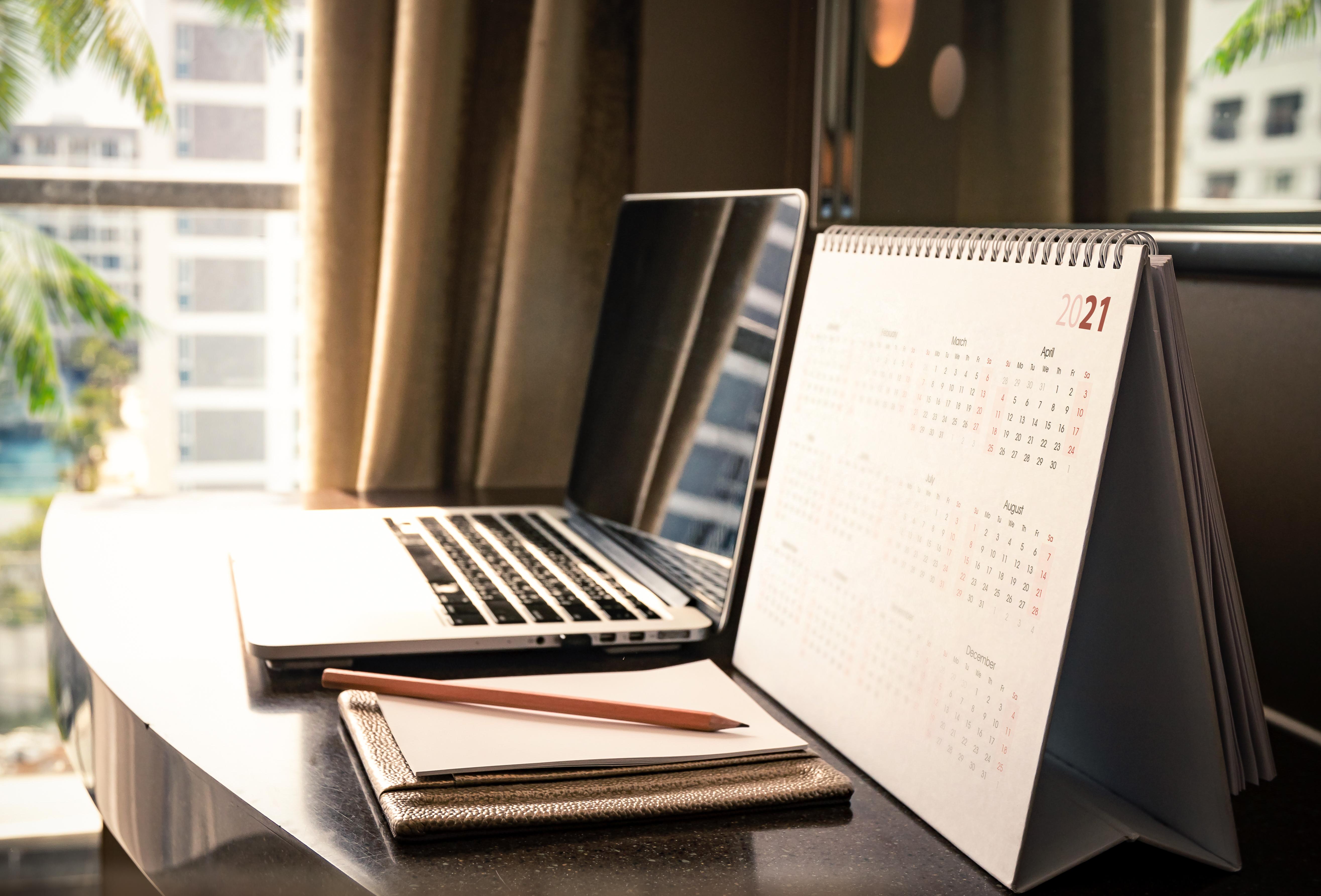 Laptop and calendar on desk