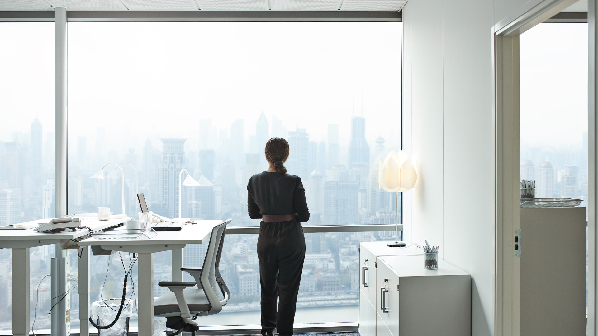 Businesswoman standing inside office and looking out of big window with beautiful view of skyline