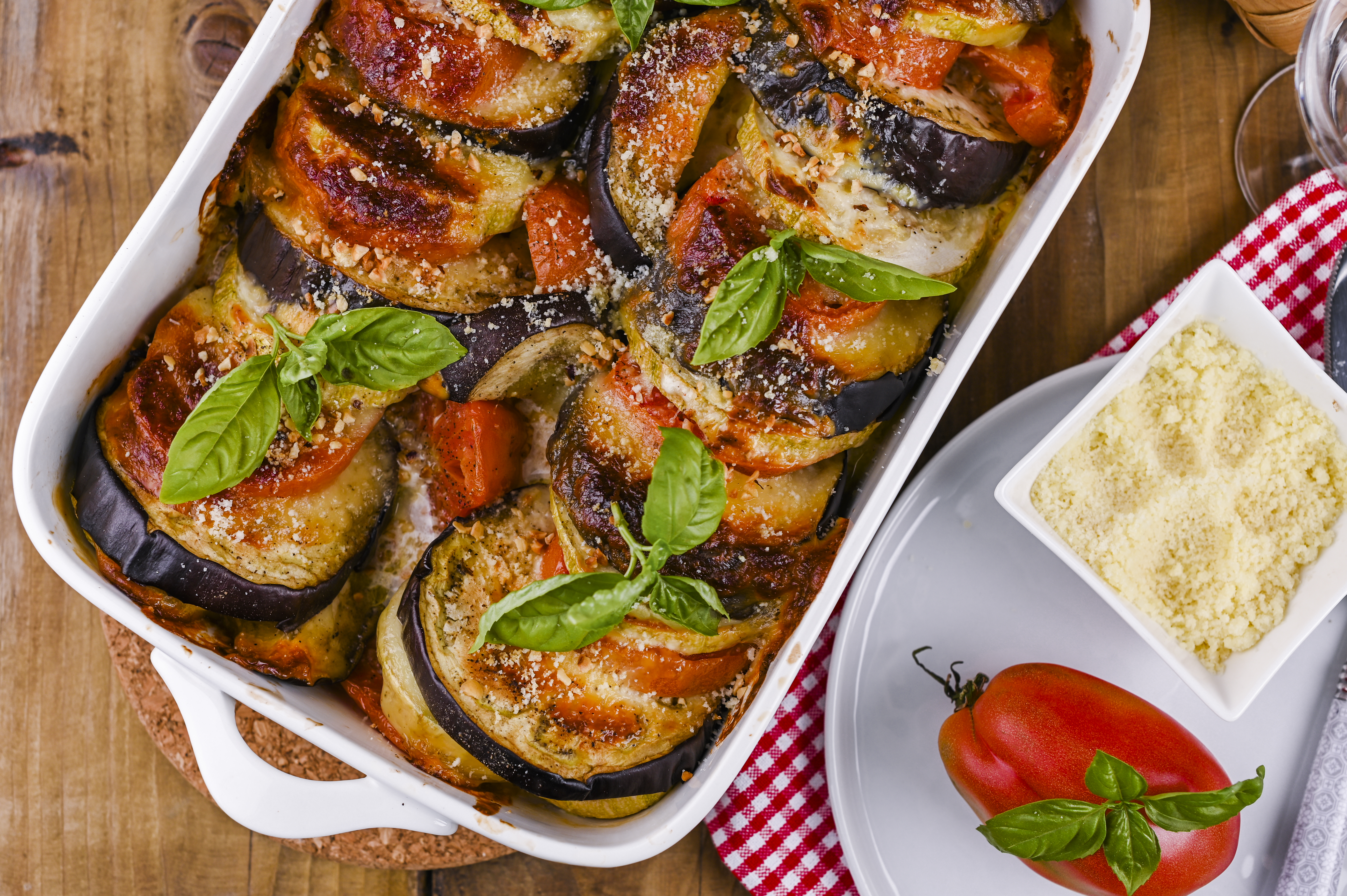Traditional italian food. Baked eggplant, tomatoes with sauce, parmesan and basil. Rustic food for a healthy diet. Vegetables for lunch.