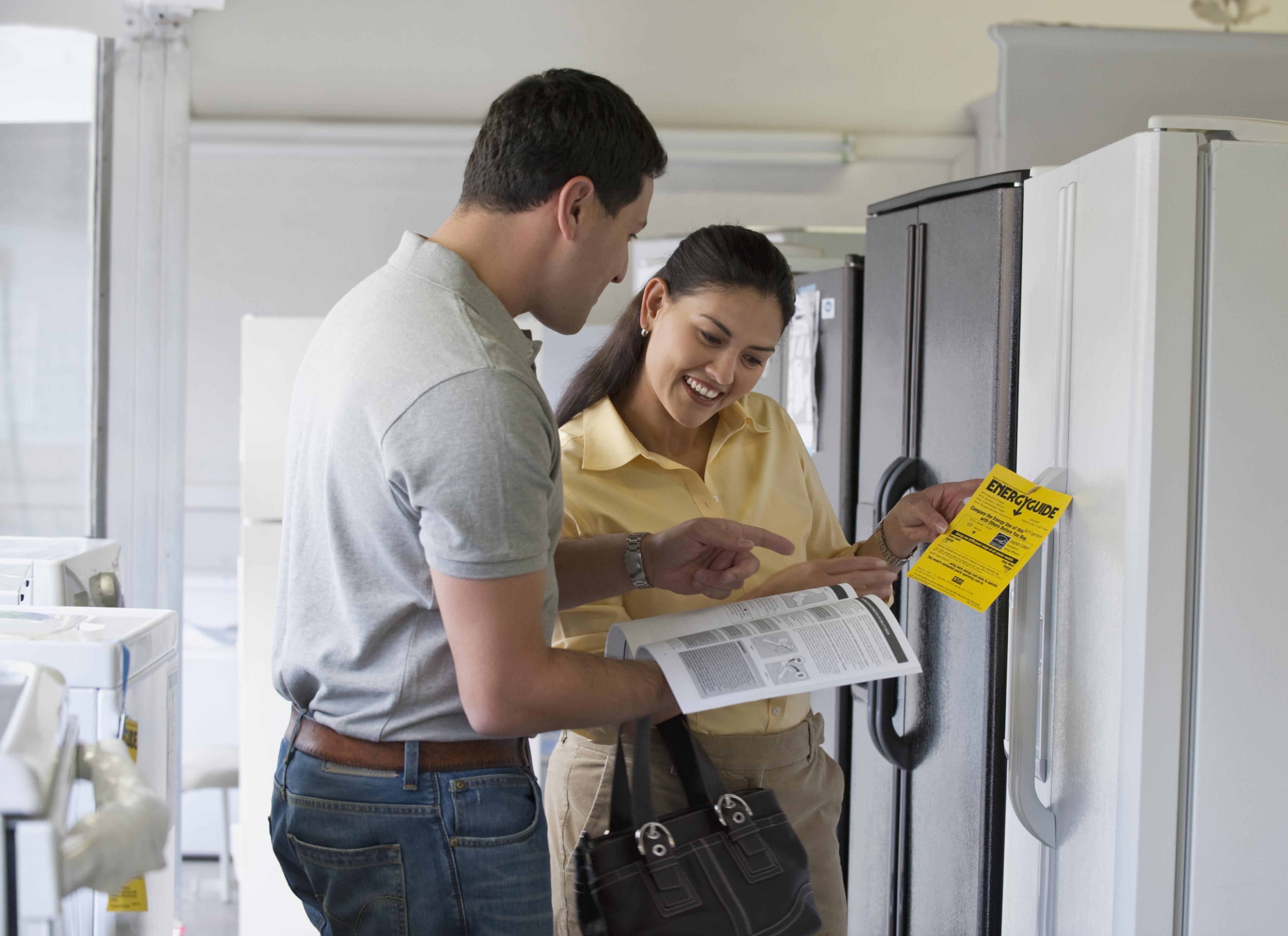 Hispanic couple shopping for refrigerator